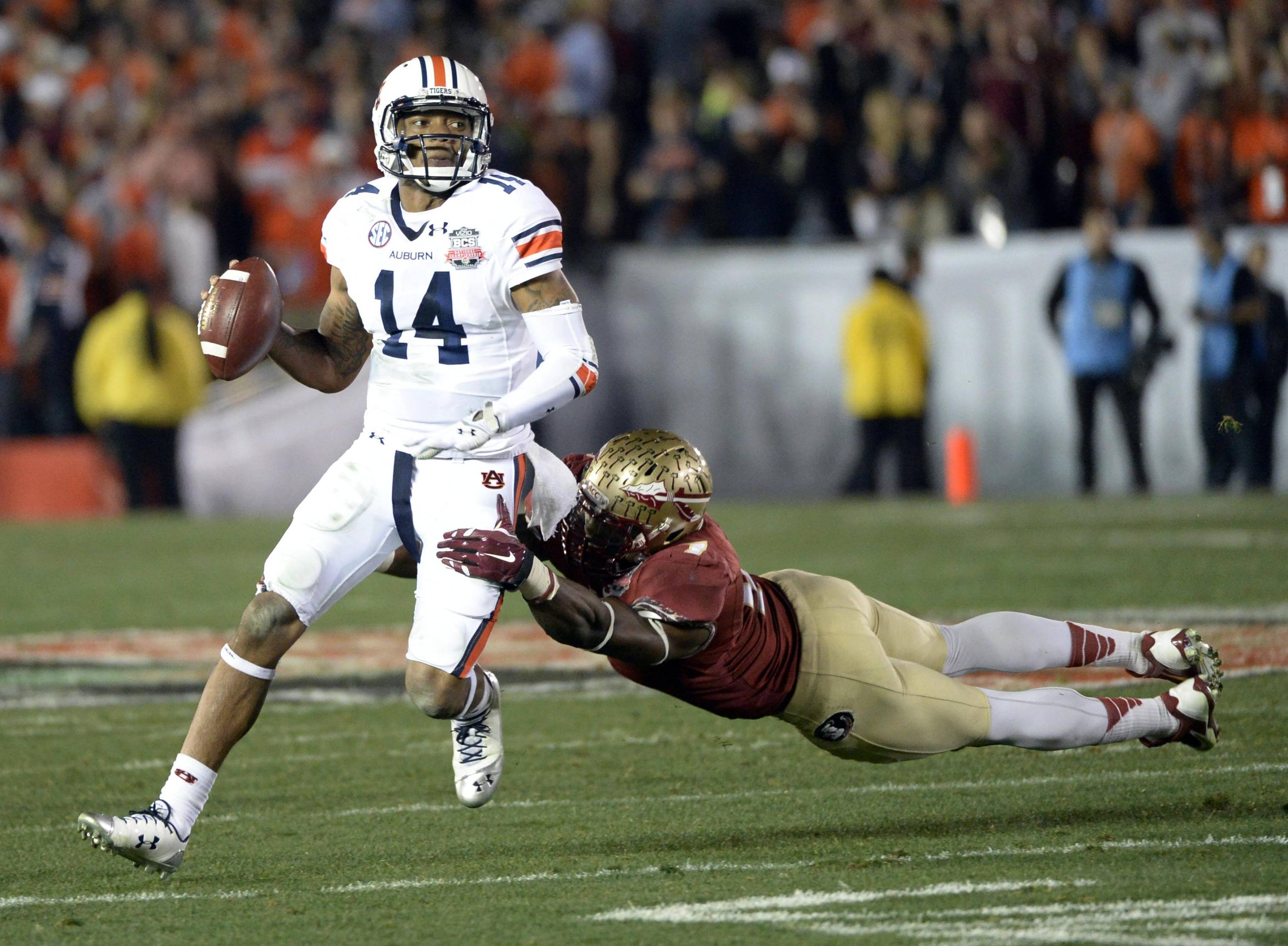 Jan 6, 2014; Pasadena, CA, USA; Florida State Seminoles linebacker Christian Jones (7) tries to tackle Auburn Tigers quarterback Nick Marshall (14) during the first half of the 2014 BCS National Championship game at the Rose Bowl.  Mandatory Credit: Richard Mackson-USA TODAY Sports