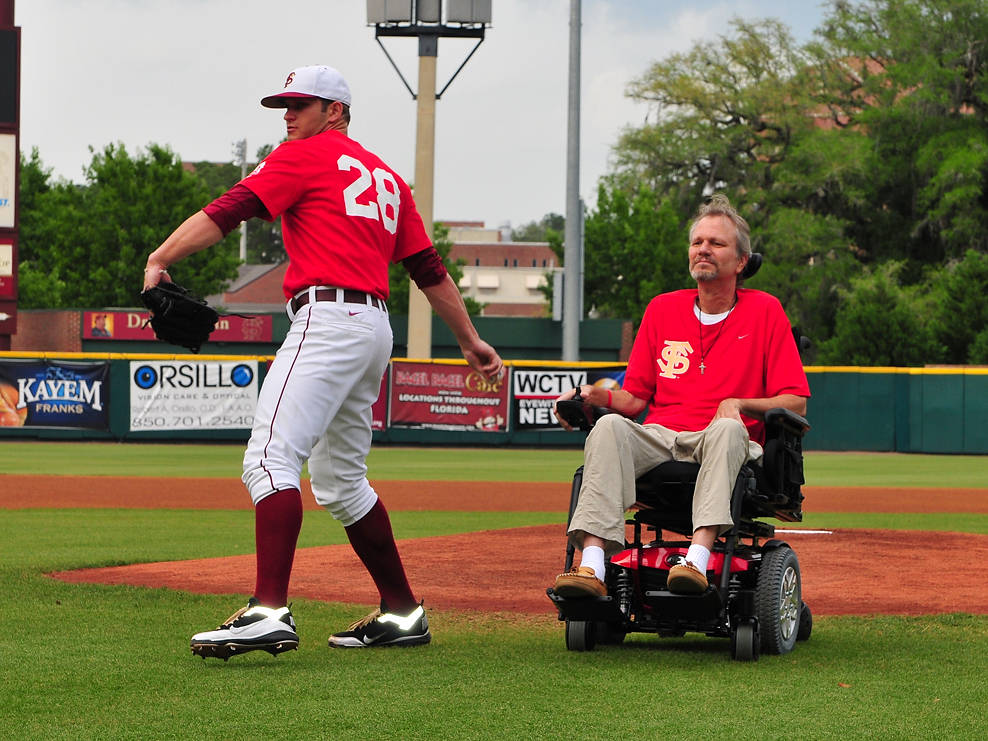 FSU senior Tyler Everett throws out the ceremonial first pitch after taking the ball from his father Jimmy Everett prior to Wednesday's ALS Awareness game.