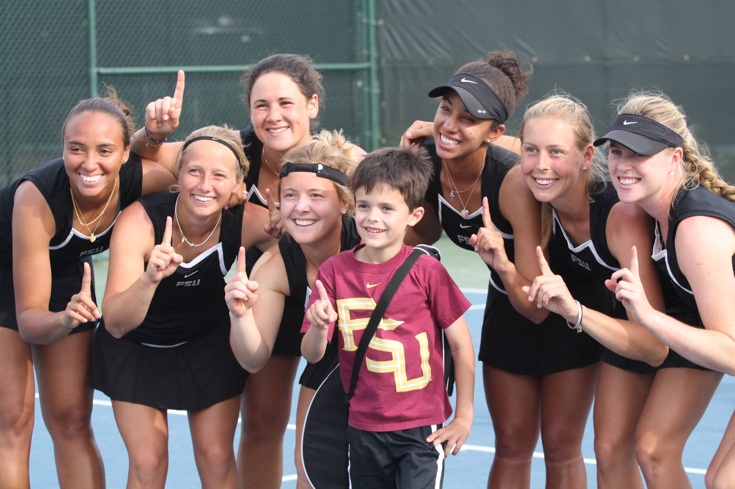 The team smiles with a young FSU tennis fan.