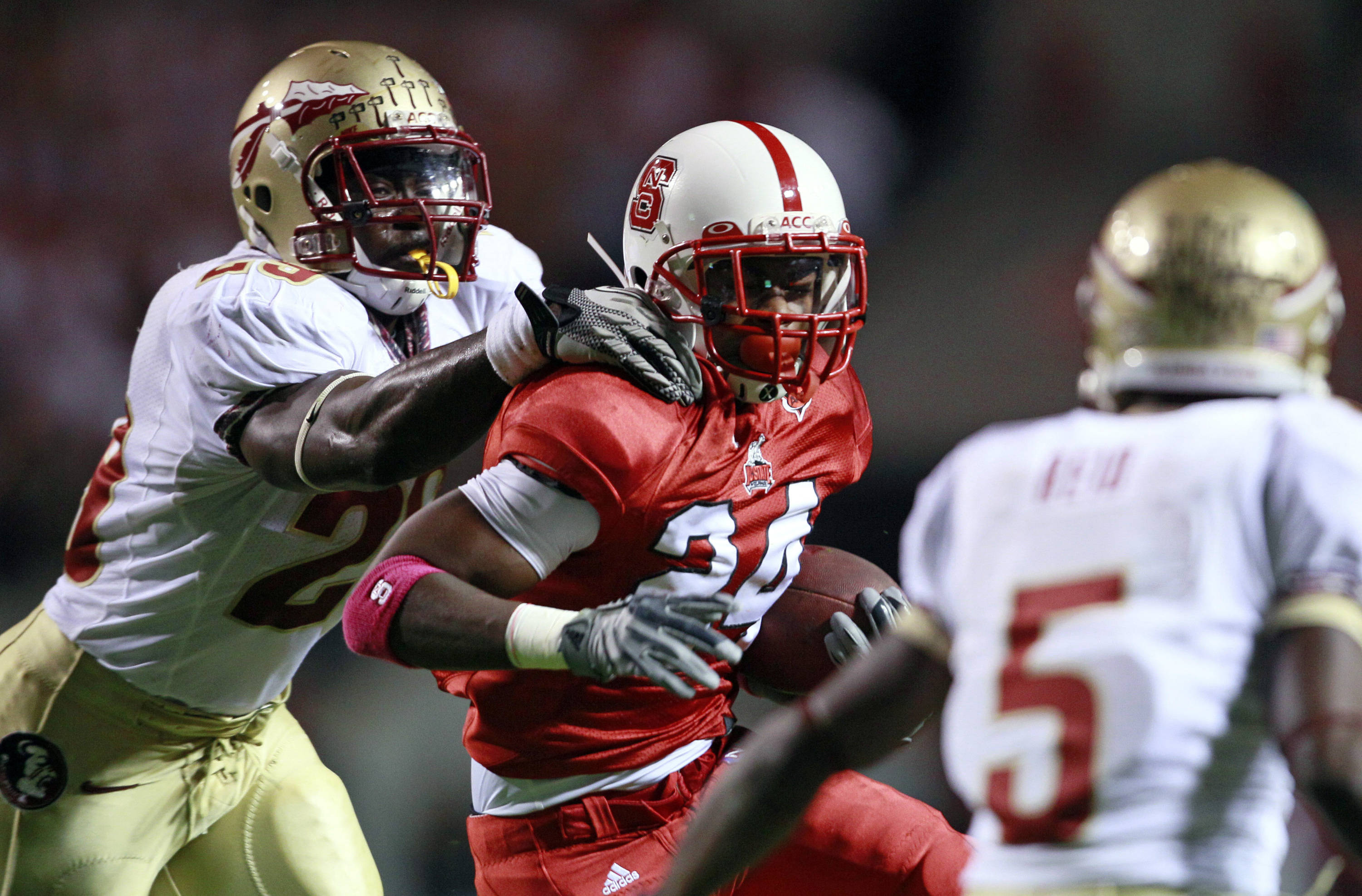 Florida State's Kendall Smith and Greg Reid (5) move in to tackle North Carolina State's James Washington (24) during the first half of an NCAA college football game in Raleigh, N.C., Thursday, Oct. 28, 2010. (AP Photo/Gerry Broome)