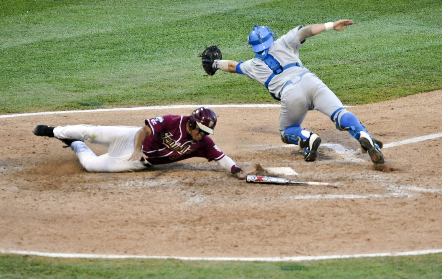 Florida State's Devon Travis, left, scores at home plate against UCLA catcher Tyler Heineman on a throwing error of third baseman Kevin Kramer, in the fourth inning. Florida State's Steven Rodriguez also scored on the play. (AP Photo/Dave Weaver)
