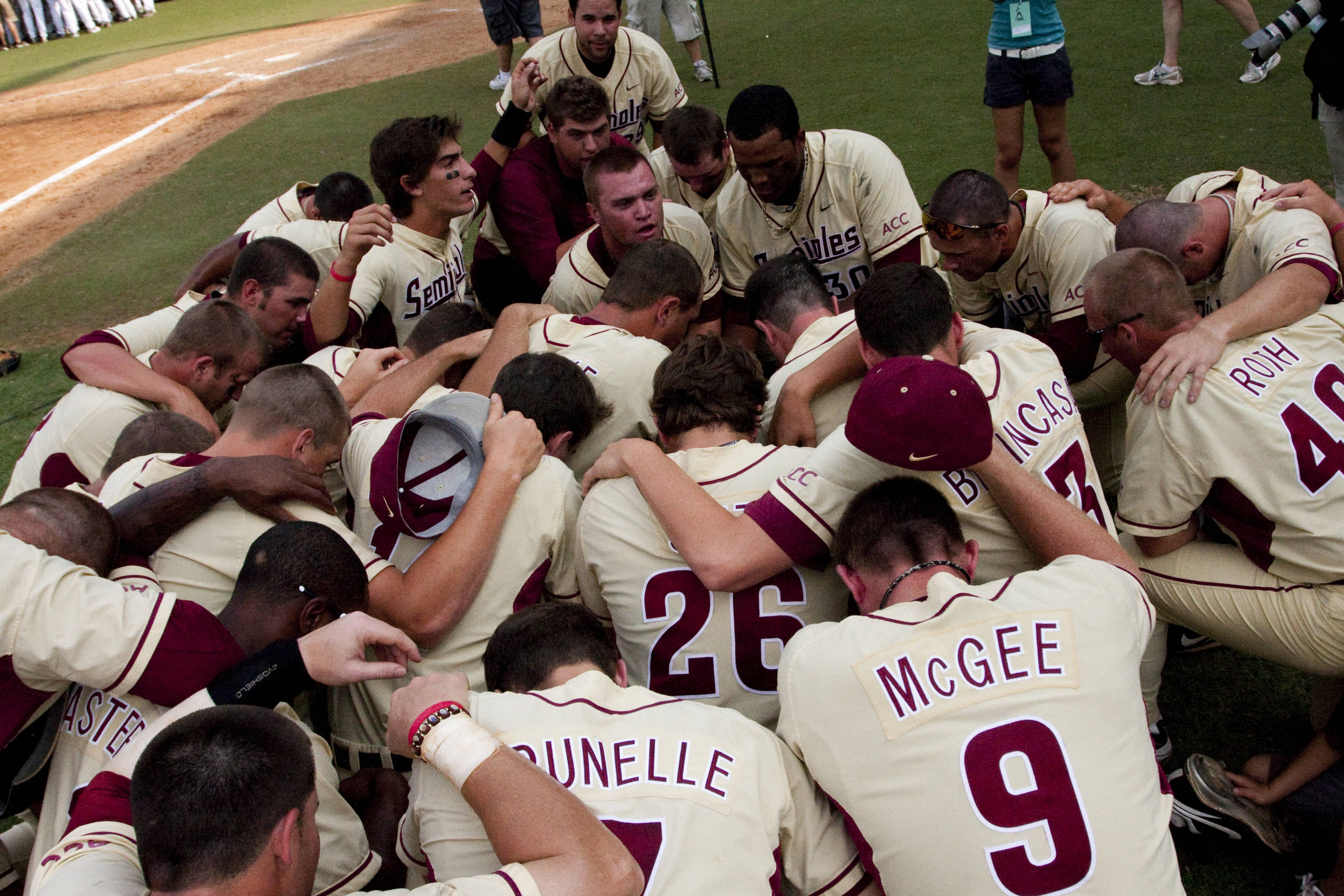 The team huddles on the field after winning game three against Vanderbilt.