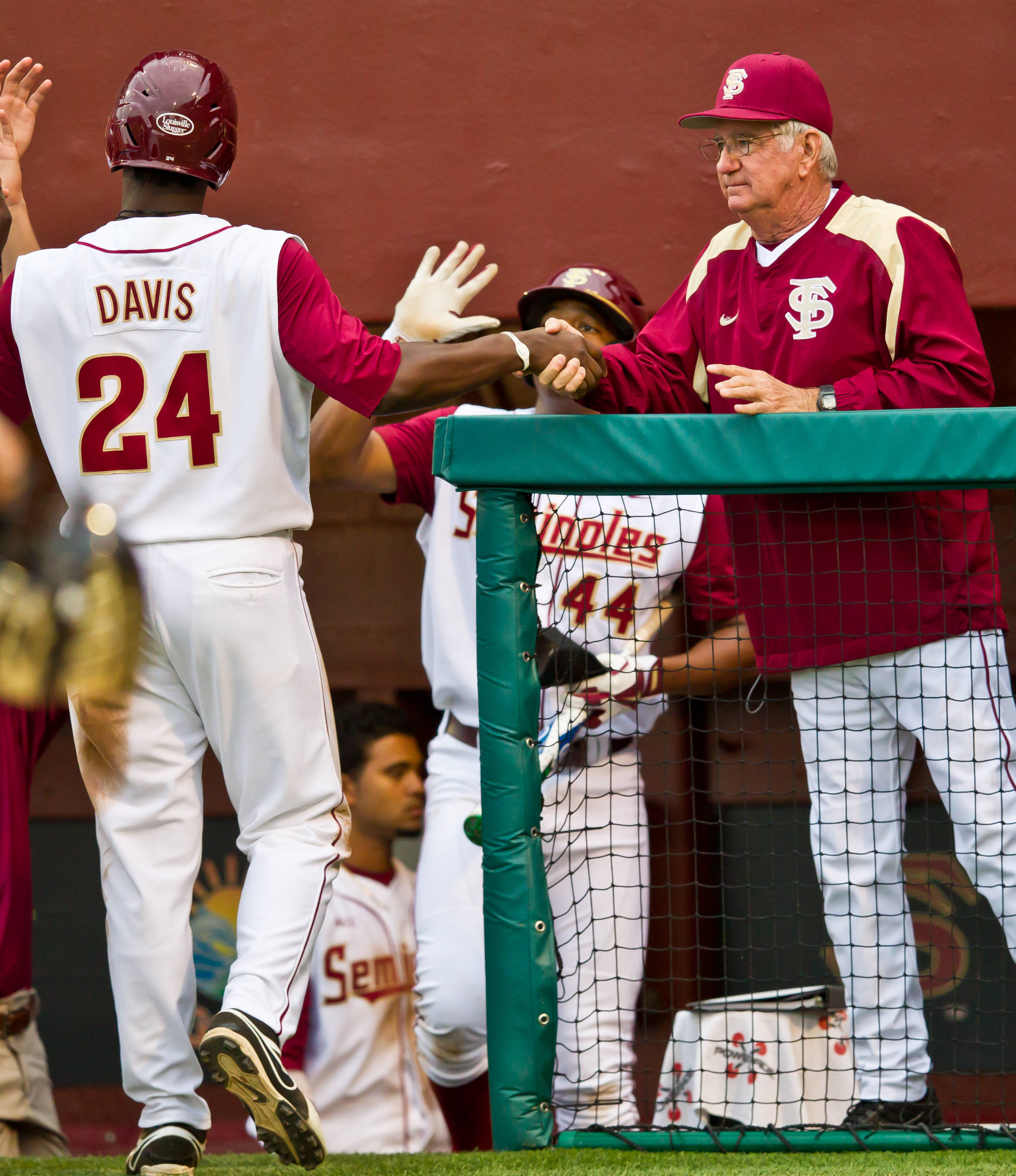 Marcus Davis is greeted inside the dugout by head coach Mike Martin