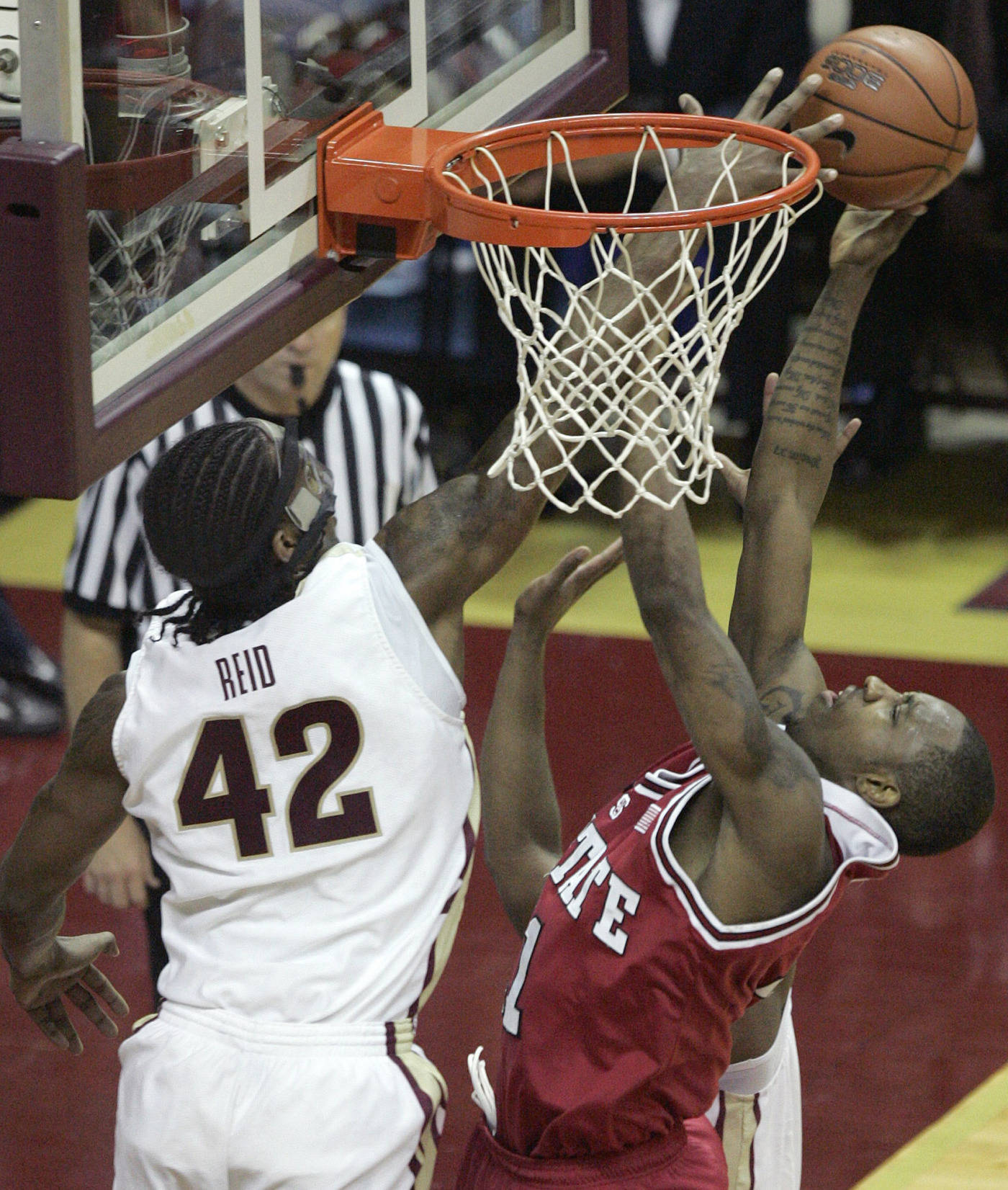 Florida State's Ryan Reid, left, blocks the shot of North Carolina State's Gavin Grant in the second half of a college basketball game Saturday, Jan. 26, 2008 in Tallahassee, Fla.