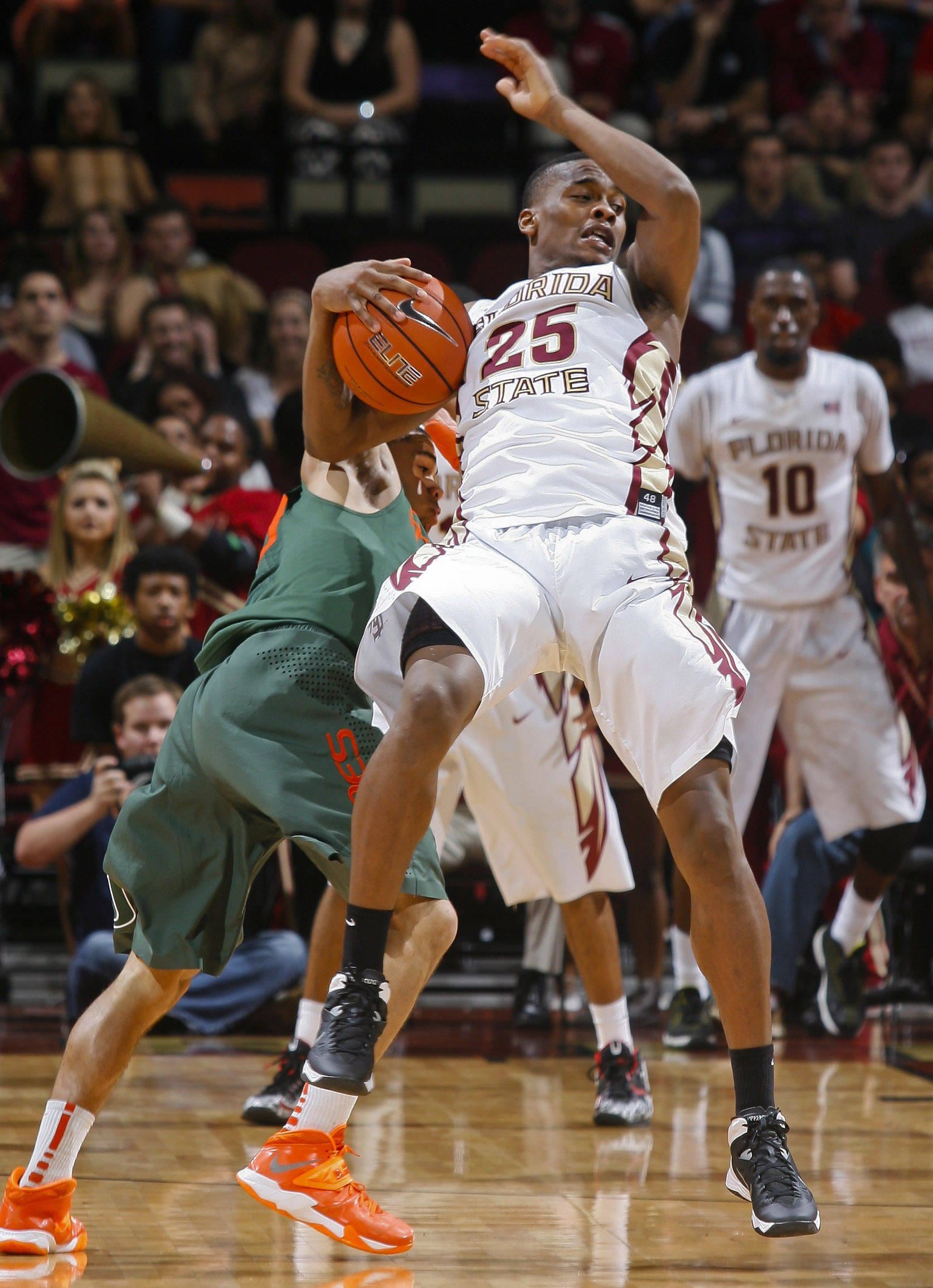 Feb 10, 2014; Tallahassee, FL, USA; Miami Hurricanes guard Manu Lecomte (20) fouls Seminoles guard Aaron Thomas (25) as they collide in the second half. Phil Sears-USA TODAY Sports