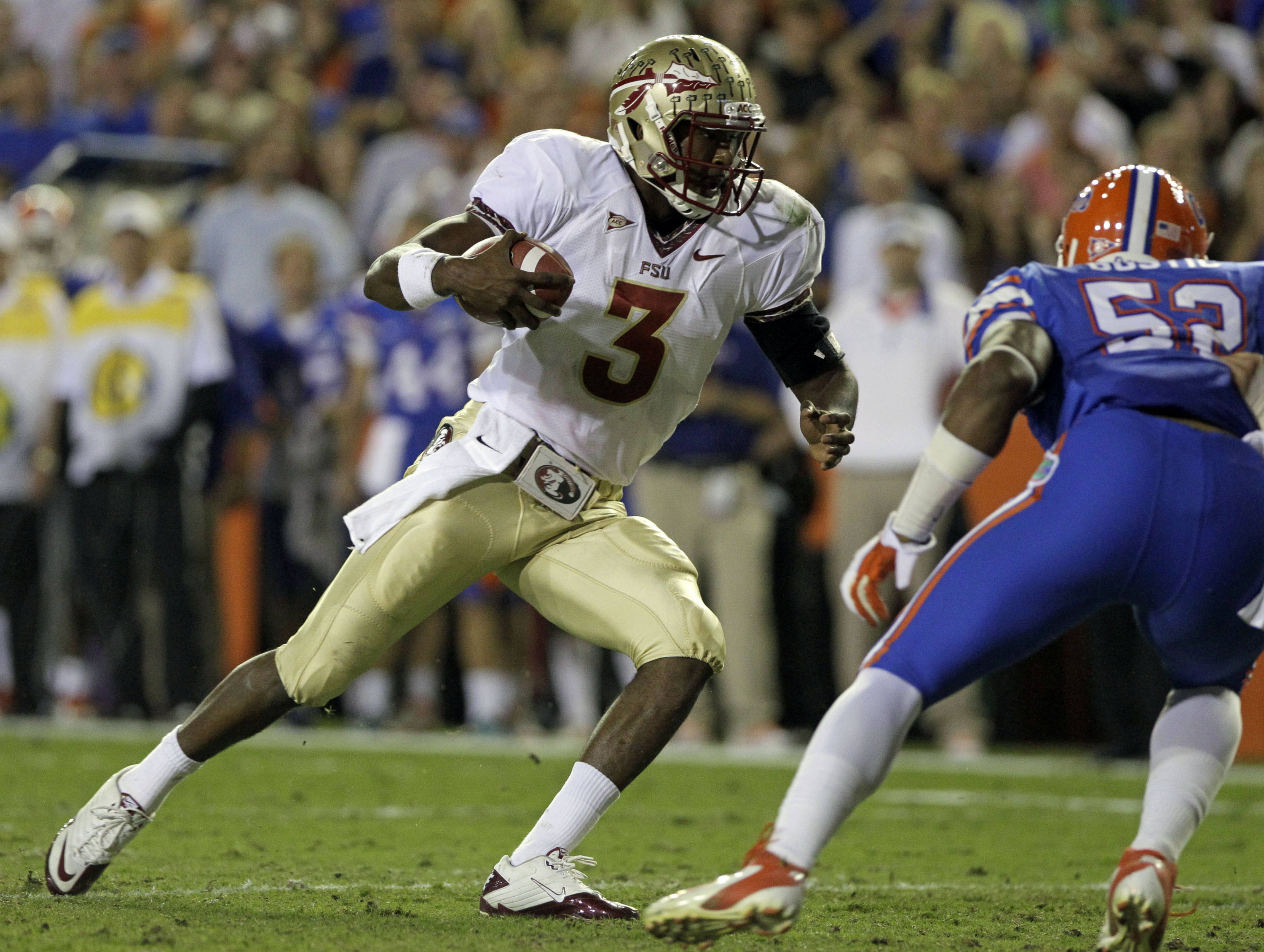 Florida State quarterback EJ Manuel (3) scrambles past Florida linebacker Jonathan Bostic (52) for a short gain during the first half of an NCAA college football game on Saturday, Nov. 26, 2011, in Gainesville, Fla. (AP Photo/John Raoux)
