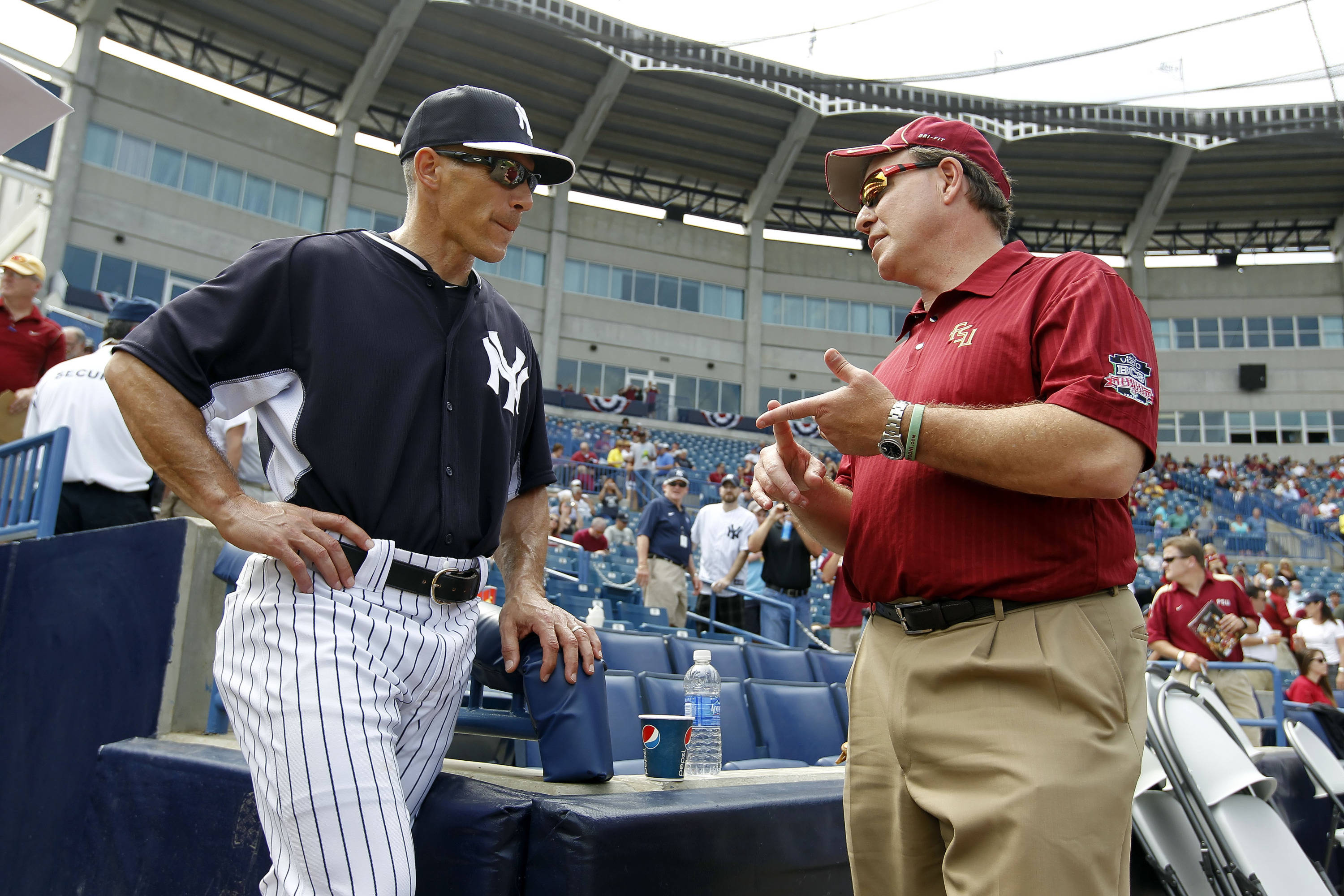 Feb 25, 2014; Tampa, FL, USA; New York Yankees manager Joe Girardi (28) and Florida State Seminoles football head coach Jimbo Fisher talk before the game at George M. Steinbrenner Field. Mandatory Credit: Kim Klement-USA TODAY Sports