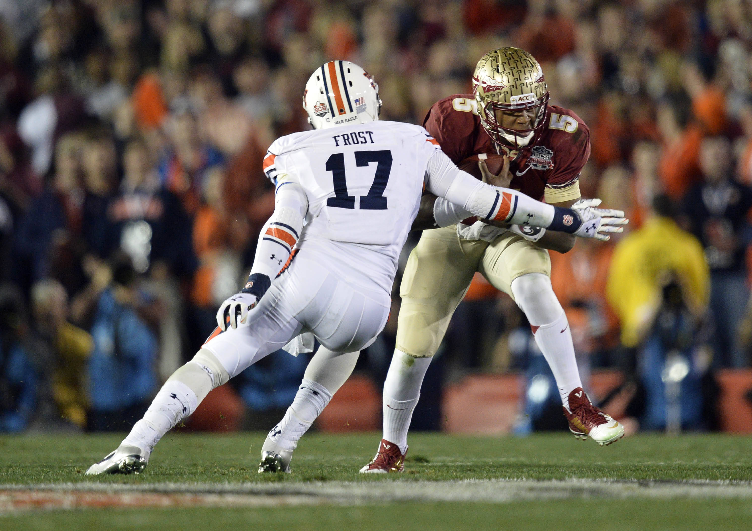 Jan 6, 2014; Pasadena, CA, USA; Florida State Seminoles quarterback Jameis Winston (5) runs against Auburn Tigers linebacker Kris Frost (17) during the first half of the 2014 BCS National Championship game at the Rose Bowl.  Mandatory Credit: Robert Hanashiro-USA TODAY Sports