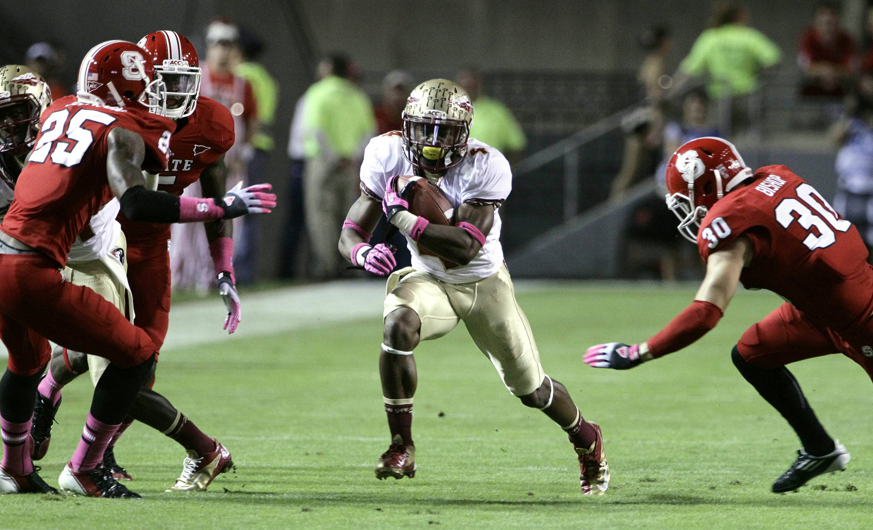 Florida State's Chris Thompson finds some running room as North Carolina State's Dontae Johnson (25) and Brandan Bishop (30) move in. (AP Photo/Gerry Broome)