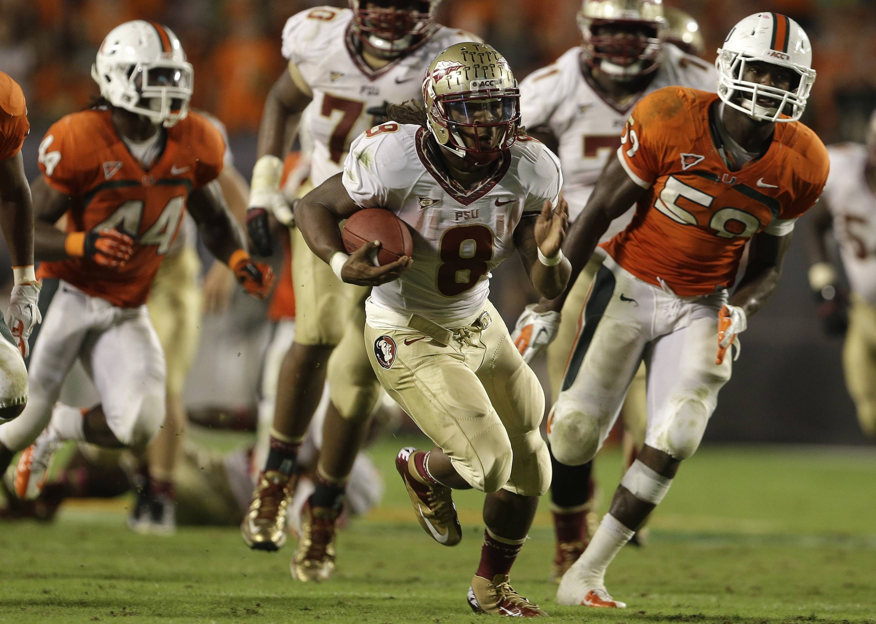 Florida State running back Devonta Freeman (8) runs for a first down past Miami linebacker Jimmy Gaines (59) during the second half of an NCAA college football game on Saturday, Oct. 20, 2012, in Miami. (AP Photo/Lynne Sladky)