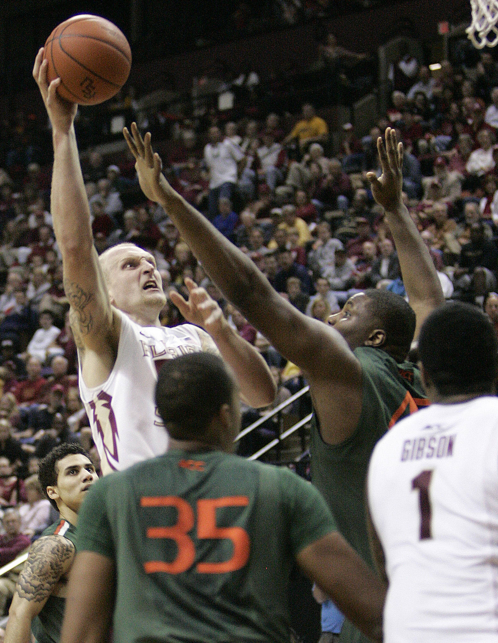 Florida State's Jon Kreft scores over the defense of Miami's Reggie Johnson in the first half of an NCAA college basketball game on Saturday, Feb. 11, 2012 in Tallahassee, Fla.(AP Photo/Steve Cannon)