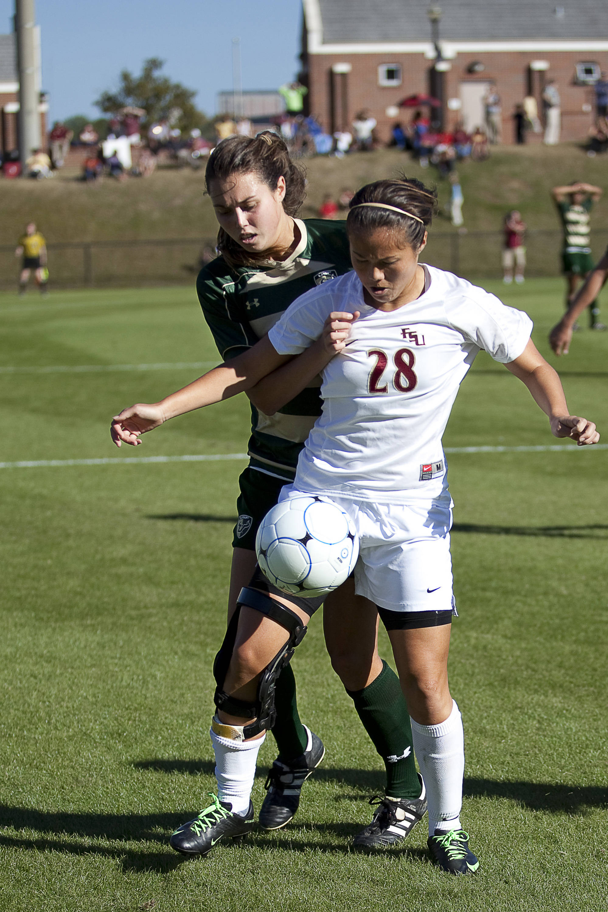 Rachel Lim (28) controls the ball before getting pulled to the ground by a USF defender