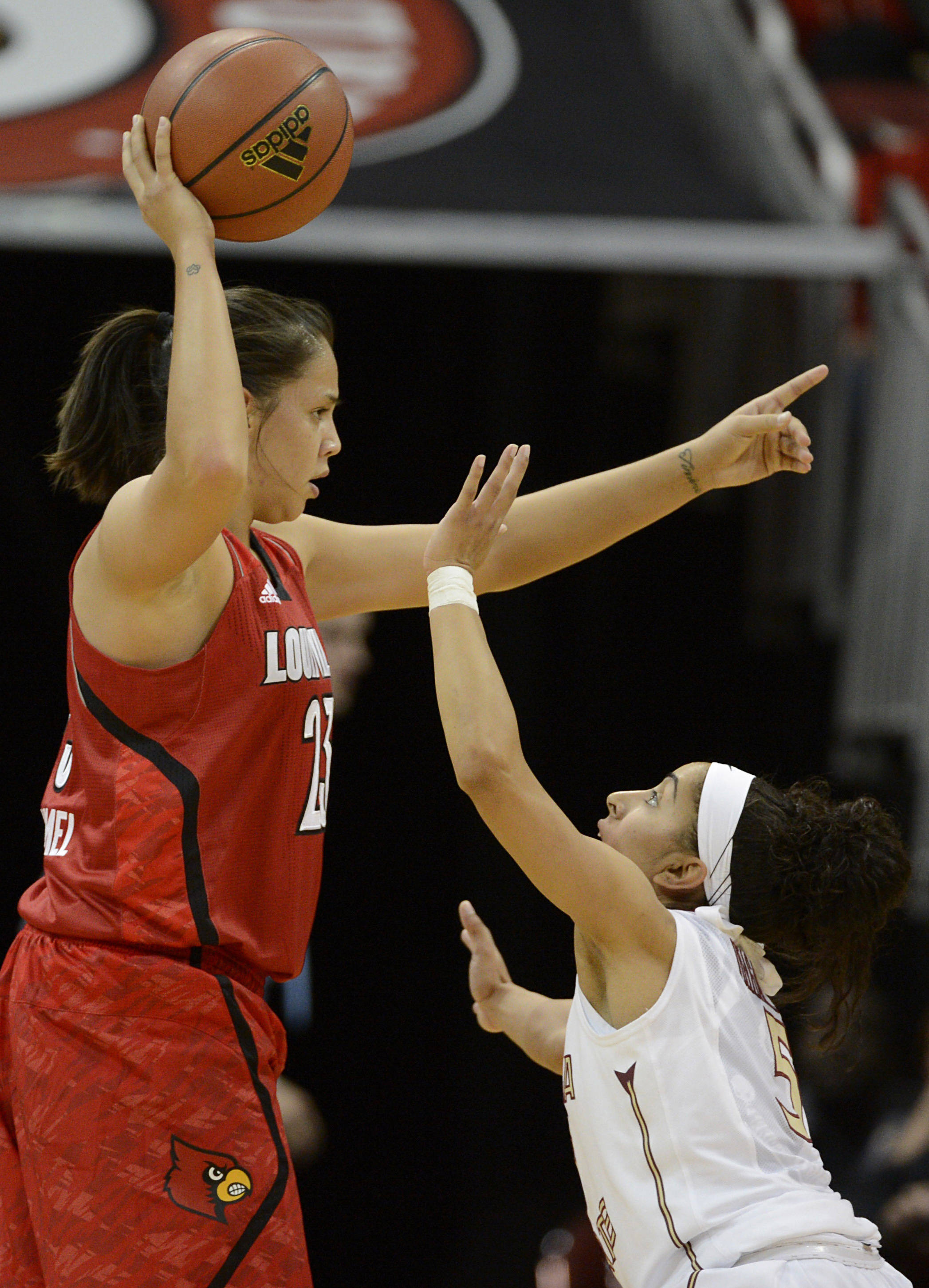 Nov 24, 2013; Louisville, KY, USA; Louisville Cardinals guard Shoni Schimmel (23) calls a play under the pressure of Florida State Seminoles guard Cheetah Delgado (5) during the first half at KFC YUM! Center. Mandatory Credit: Jamie Rhodes-USA TODAY Sports