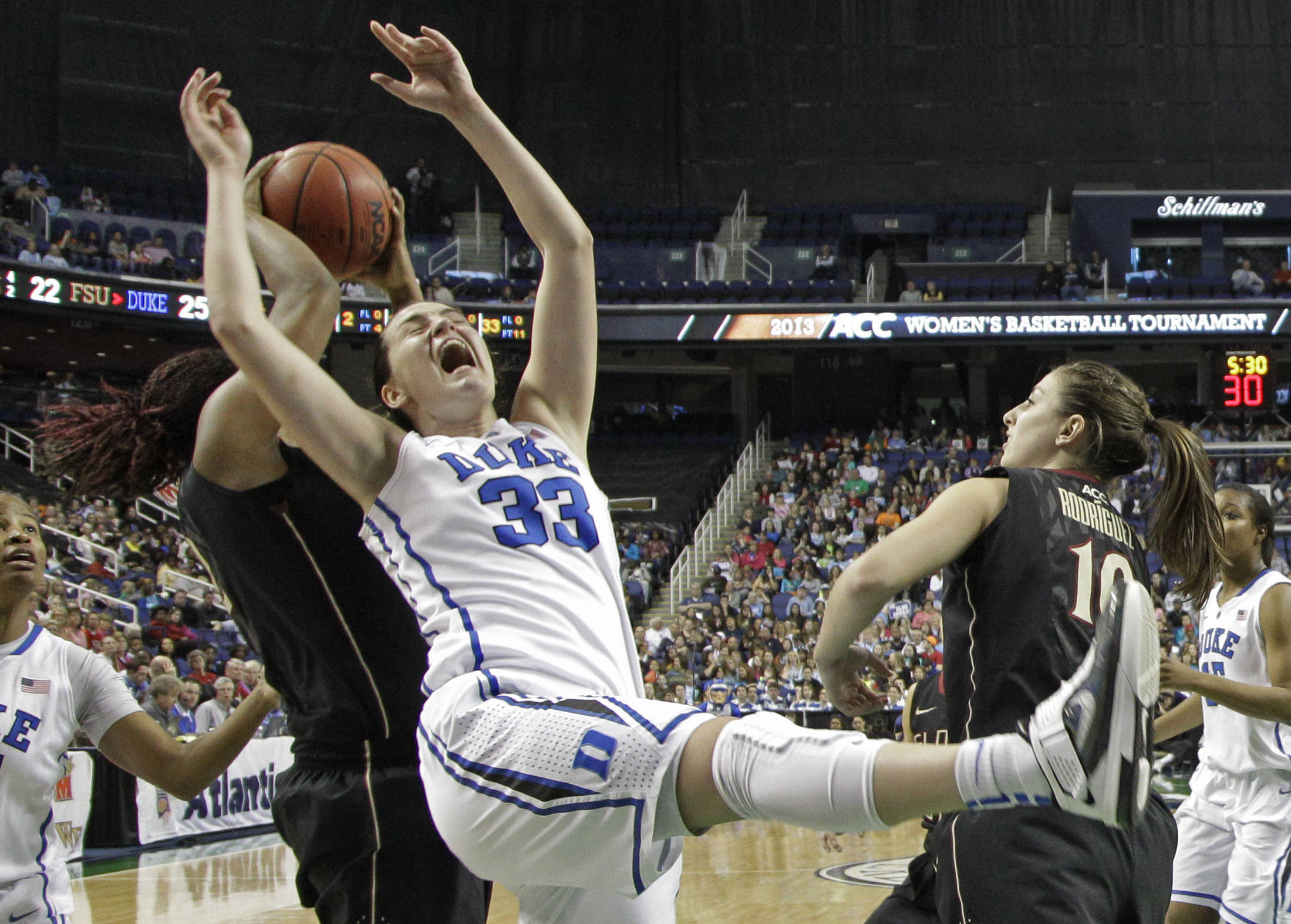 Duke's Haley Peters (33) loses the ball as she drives between Florida State's Leonor Rodriguez (10) and Lauren Coleman (32). (AP Photo/Chuck Burton)