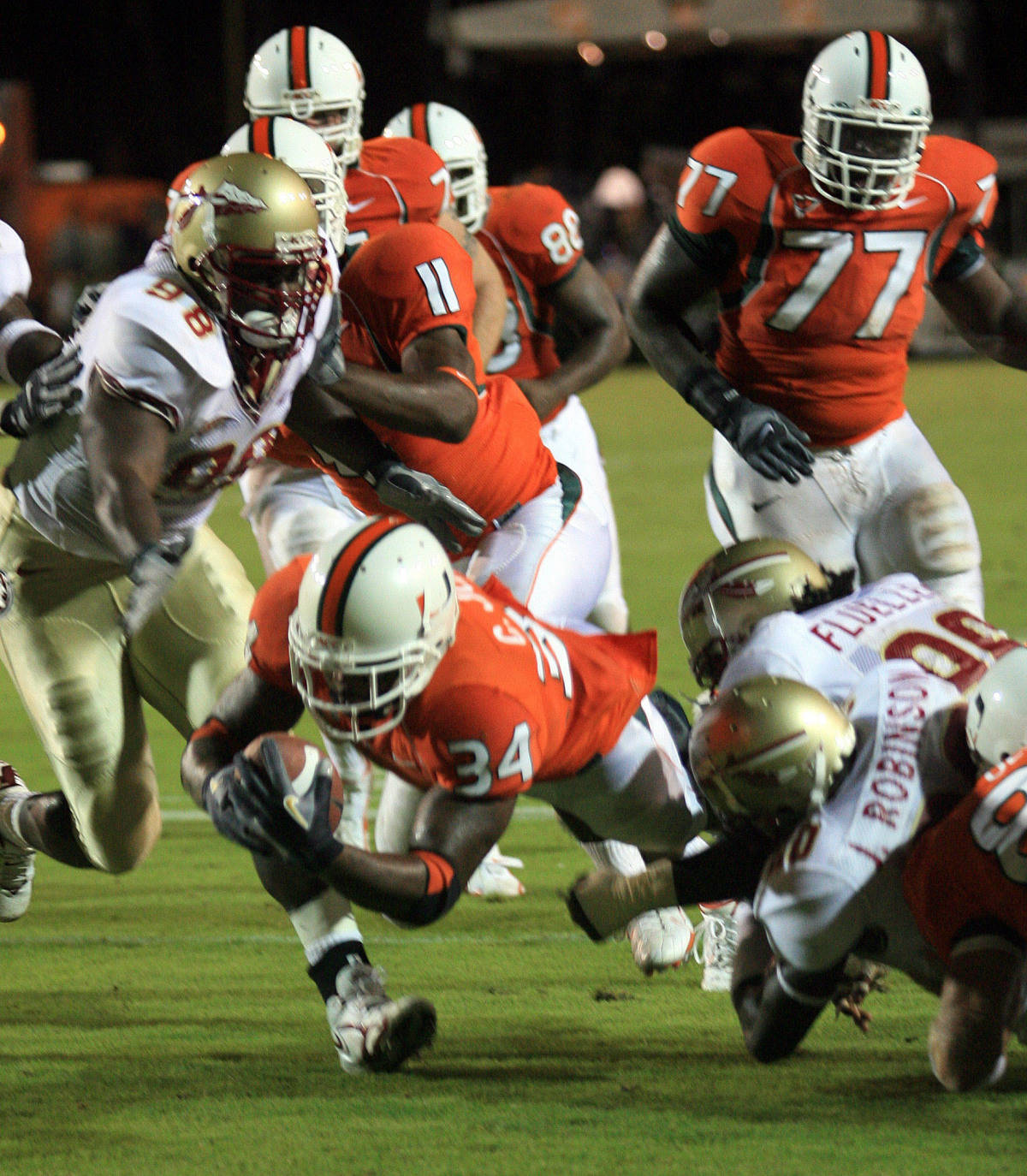 Miami runningback Charlie Jones (34) dives to the goal line for a touchdown during the second quarter of the football game against Florida State, Monday, Sept. 4, 2006 at the Orange Bowl in Miami. (AP Photo/Luis M. Alvarez)