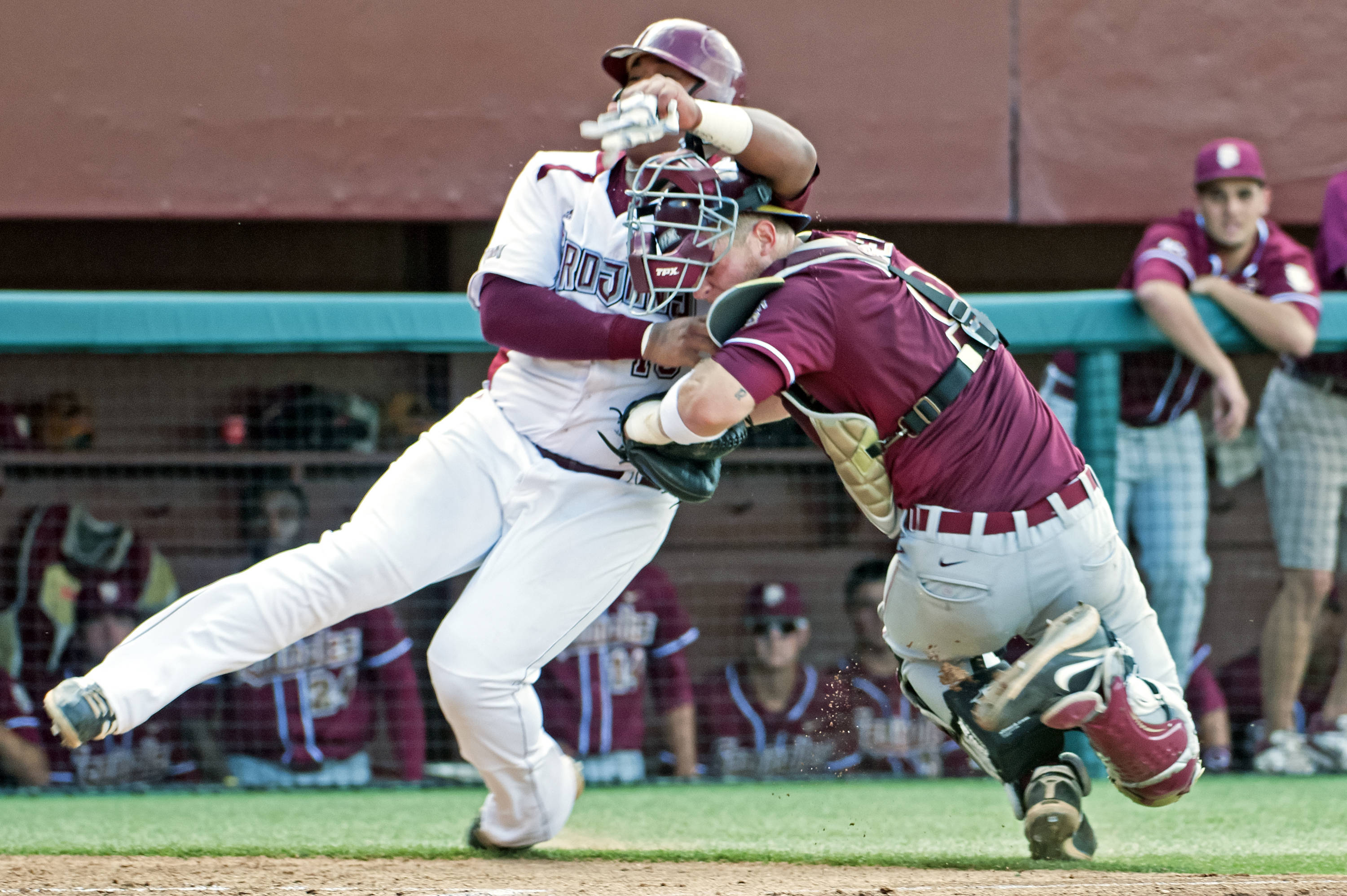 Stephen McGee (9) prevents Troy from scoring first by tagging Troy's Trae Santos at home despite a collision at the plate