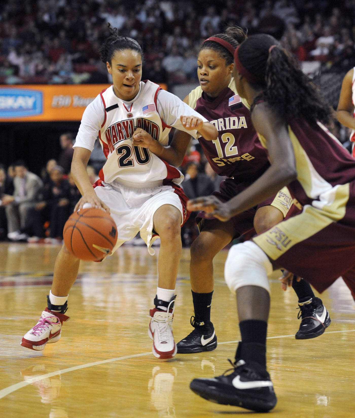 Maryland's Kristi Toliver drives the ball as Florida State's Courtney Ward (12) and Jacinta Monroe, right, defend during the first half of a college basketball game, Sunday Feb. 24, 2008 in College Park, Md. Maryland won 92-84 in overtime. (AP Photo/Gail Burton)