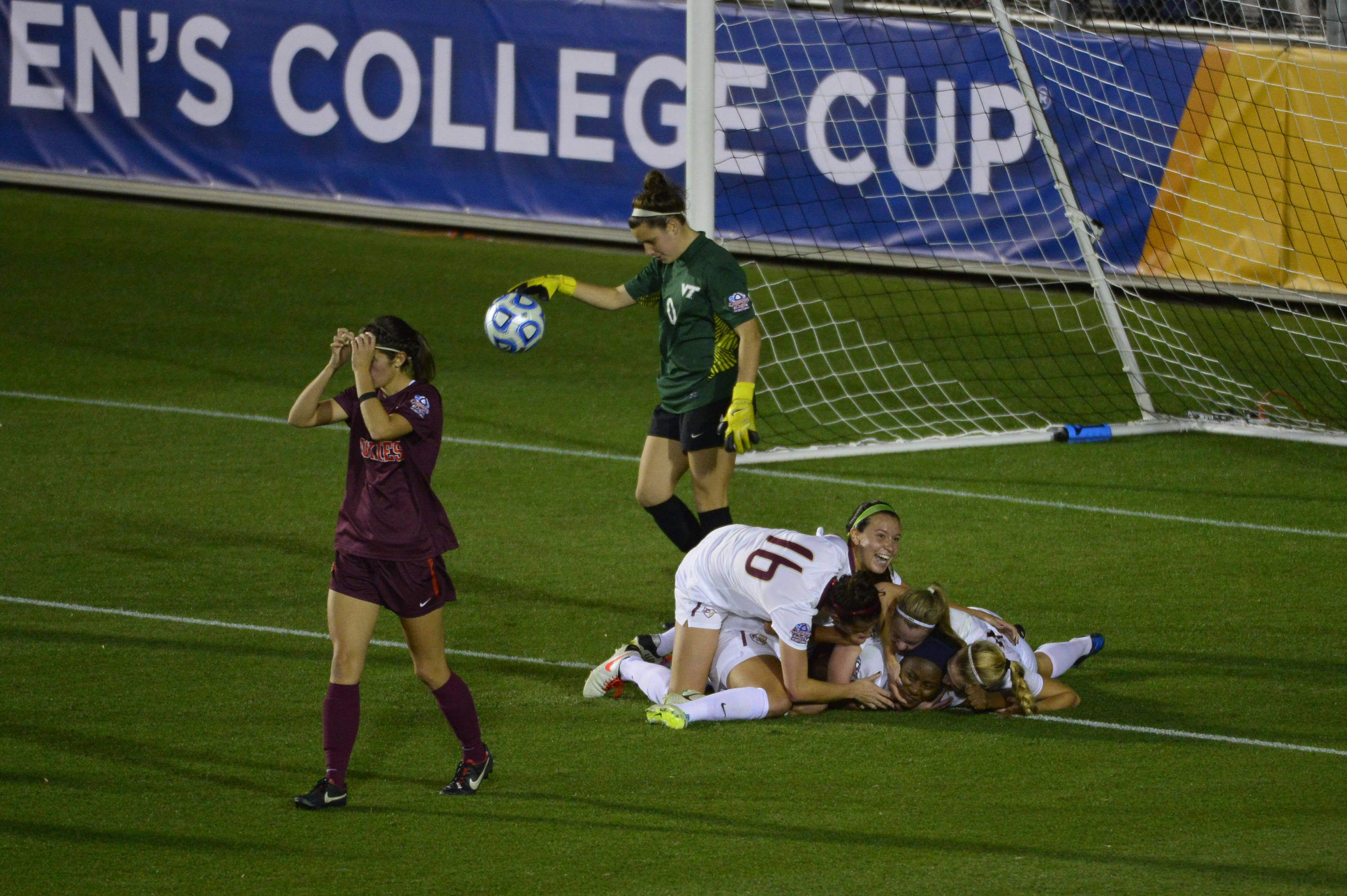 Dec 6, 2013; Cary, NC, USA; Florida State Seminoles players pile on midfielder Jamia Fields (4) after she scores a goal as Virginia Tech Hokies defender Danielle King (8) and goalkeeper Cayle Colpitts (0) look on in the second half at WakeMed Soccer Park. Mandatory Credit: Bob Donnan-USA TODAY Sports