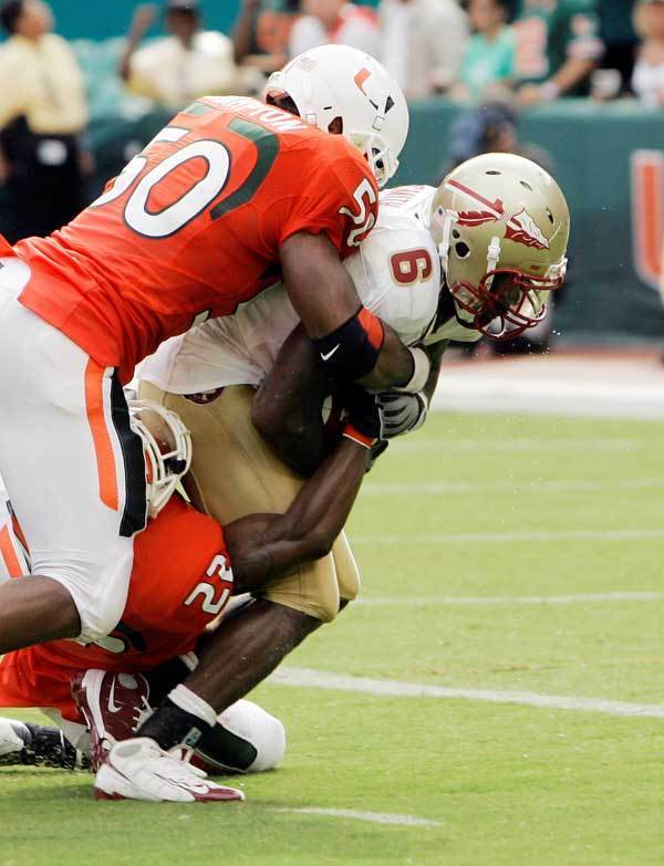 Florida State's Antone Smith (6) is tackled by Miami's Romeo Davis, left, and Bruce Johnson (22) as Smith goes on to score a touchdown in the second quarter.