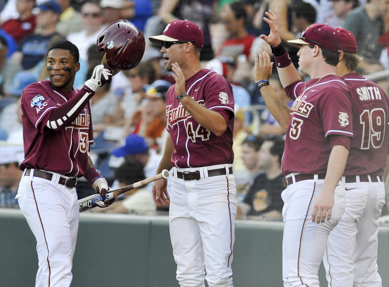 Florida State's Sherman Johnson, left, is greeted at the dugout by teammate Mack Waugh (44) after he scored against UCLA on a walk by Stephen McGee with bases loaded, in the first inning. (AP Photo/Eric Francis)