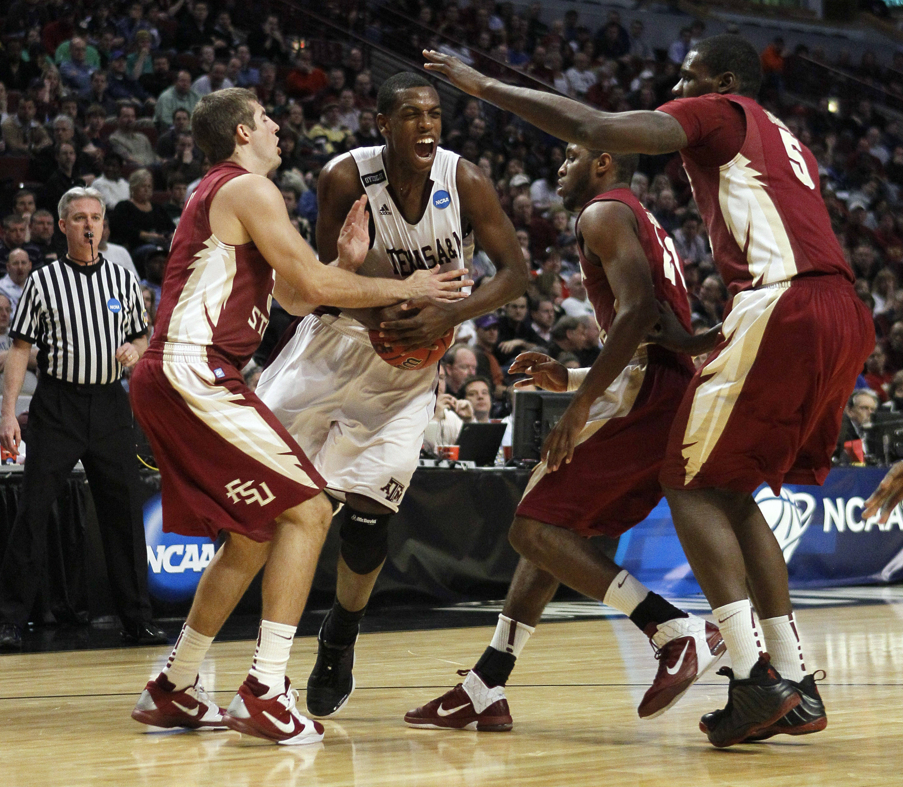 Texas A&M's Khris Middleton is defended by Florida State players Florida State's Luke Loucks, left, Michael Snaer and Bernard James, right, in the second half. (AP Photo/Charles Rex Arbogast)