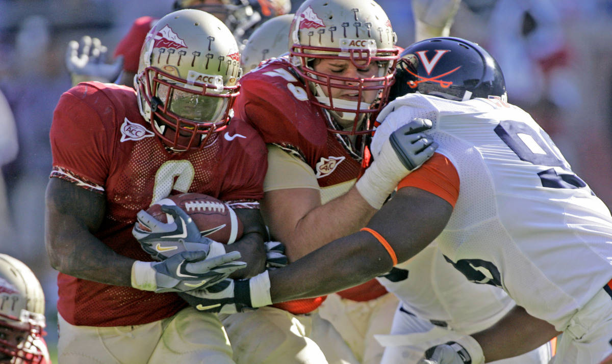 Florida State running back Antone Smith, left, runs behind the block of teammate David Overmyer, center, as he blocks Virginia's Nate Collins during the fourth quarter of a college football game Saturday, Nov. 4, 2006, in Tallahassee, Fla. FSU won 33-0. (AP Photo/Phil Coale)
