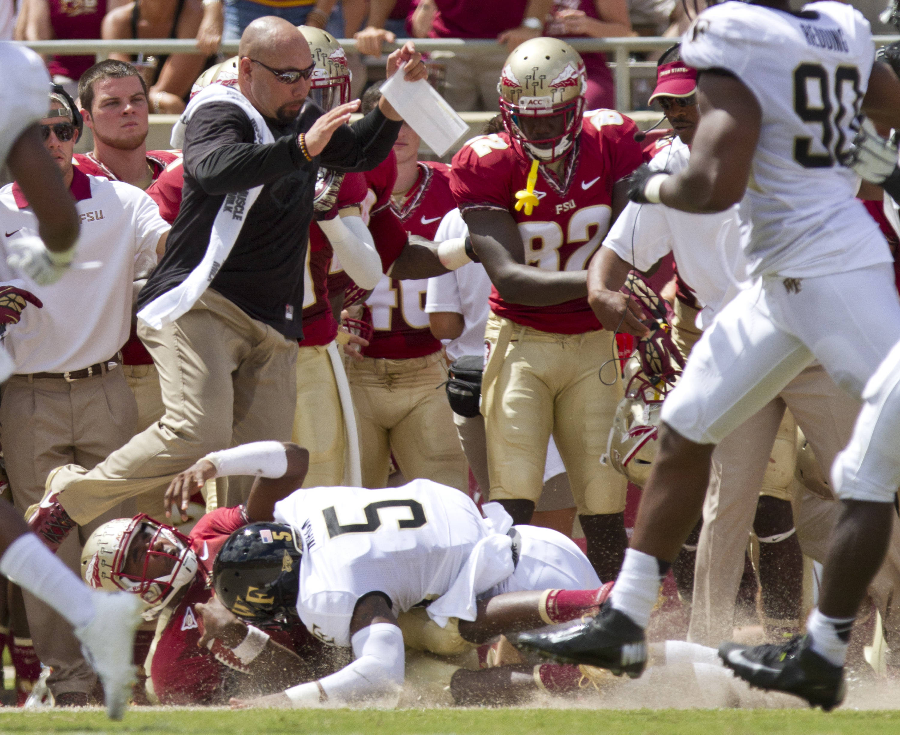 People on the FSU sideline jump to avoid being hit by players.