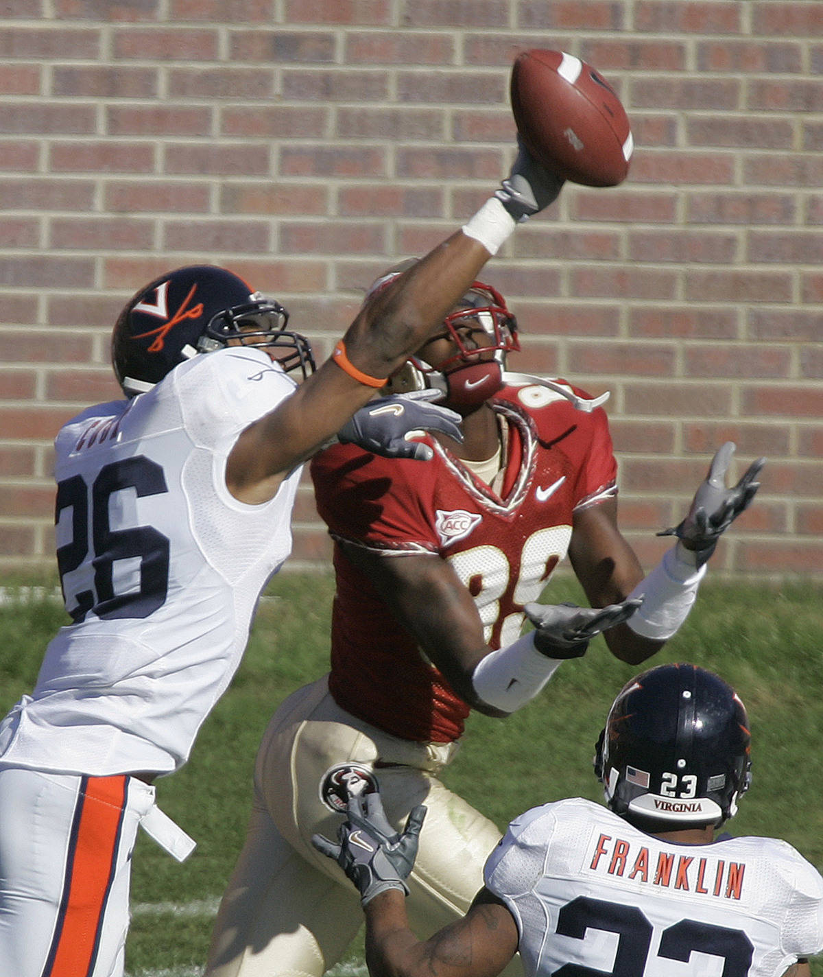 Virginia defender Chris Cook, left, knocks the ball away from Florida State receiver Greg Carr during the third quarter of a college football game, Saturday, Nov. 4, 2006, in Tallahassee, Fla. Florida State won, 33-0. Virginia's Tony Franklin, bottom right, closes in on the play. (AP Photo/Phil Coale)