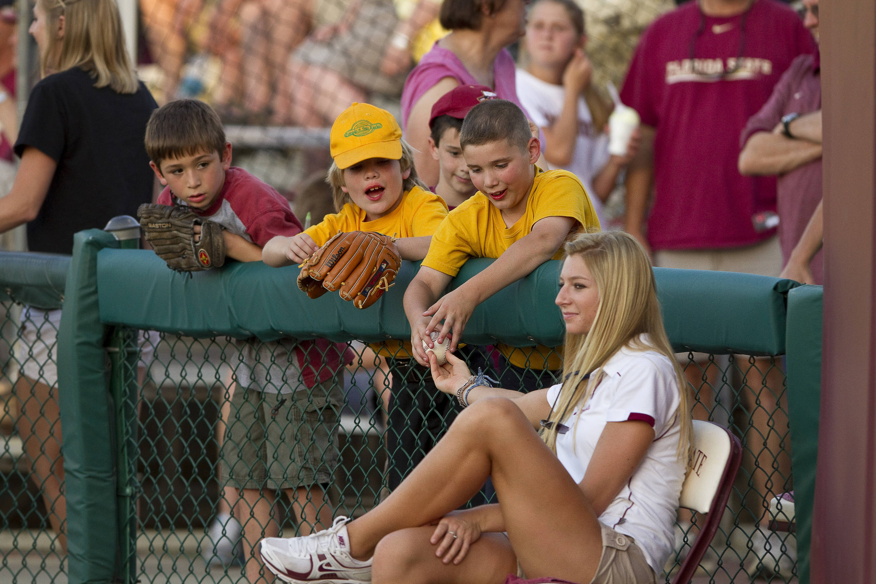 An FSU ball girl passes a foul ball to a group of young fans.