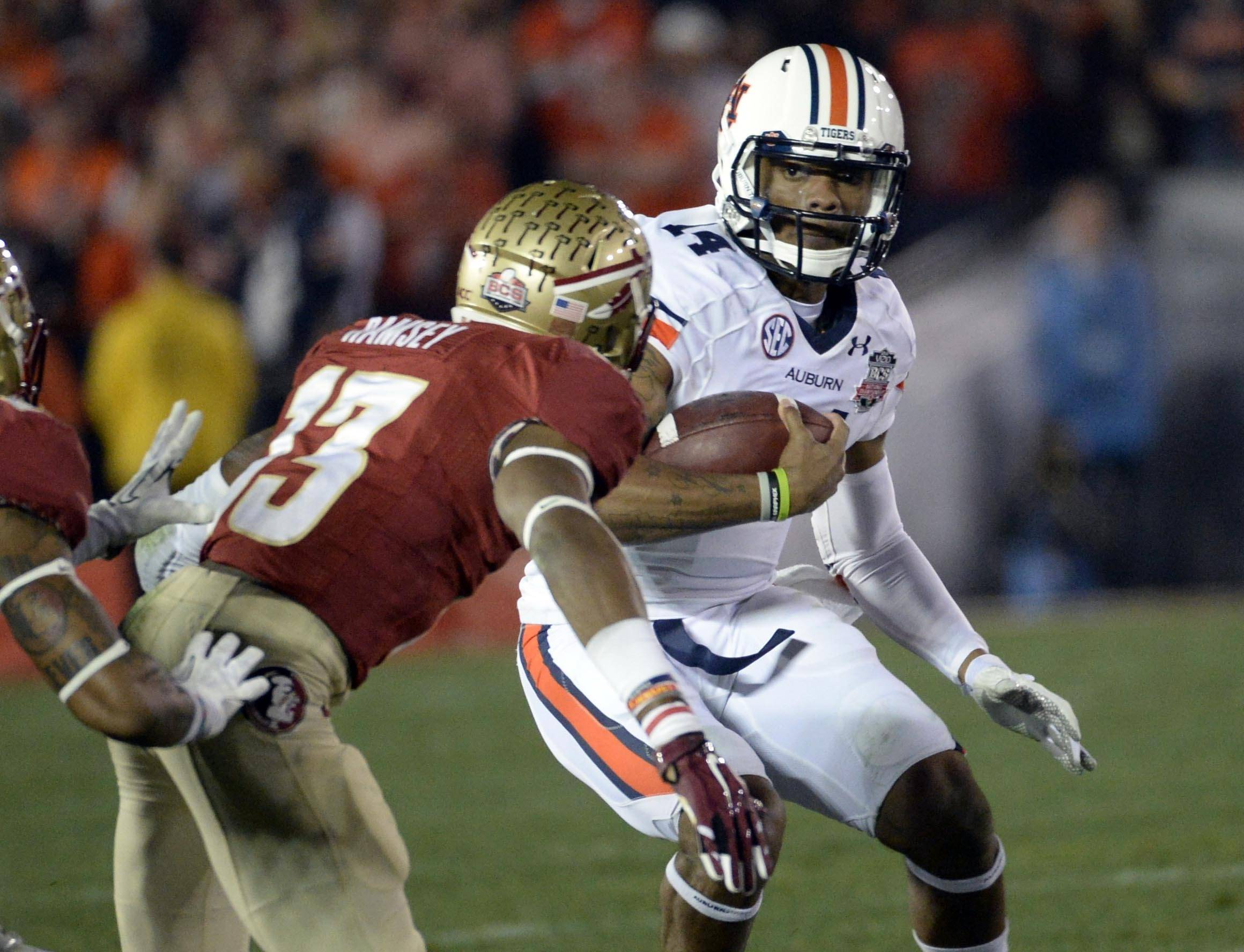 Jan 6, 2014; Pasadena, CA, USA; Auburn Tigers quarterback Nick Marshall (14) runs under pressure from Florida State Seminoles defensive back Jalen Ramsey (13)during the first half of the 2014 BCS National Championship game at the Rose Bowl.  Mandatory Credit: Richard Mackson-USA TODAY Sports