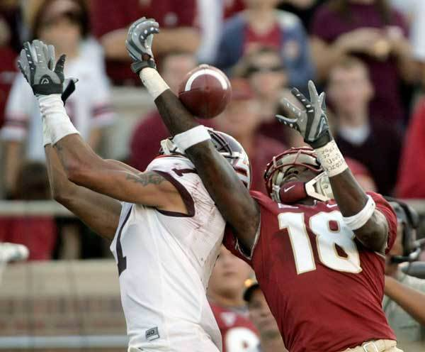 Florida State wide receiver Greg Carr, right, makes a third-quarter catch despite the defensive efforts of Virginia Tech cornerback Victor Harris.