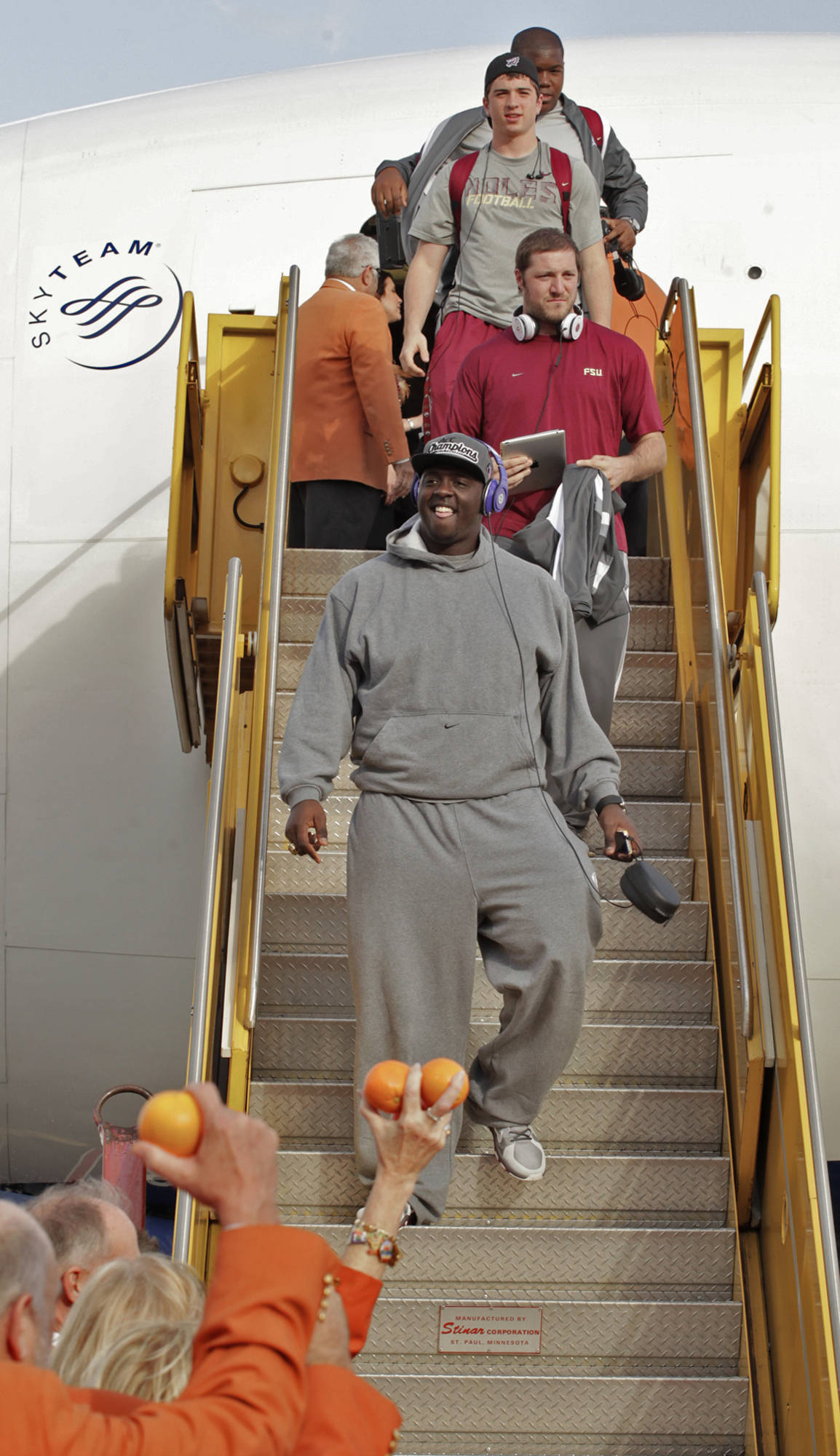 Florida State's Cameron Erving, center, smiles as he leads other players down the stairs while deplaning and being welcome by Orange Bowl Committee members, Wednesday, Dec. 26, 2012, after the Seminoles arrived in Fort Lauderdale, Fla., for the Orange Bowl Classic NCAA college football game against Northern Illinois in Miami, Jan. 1, 2013. (AP Photo/The Miami Herald, Carl Juste)