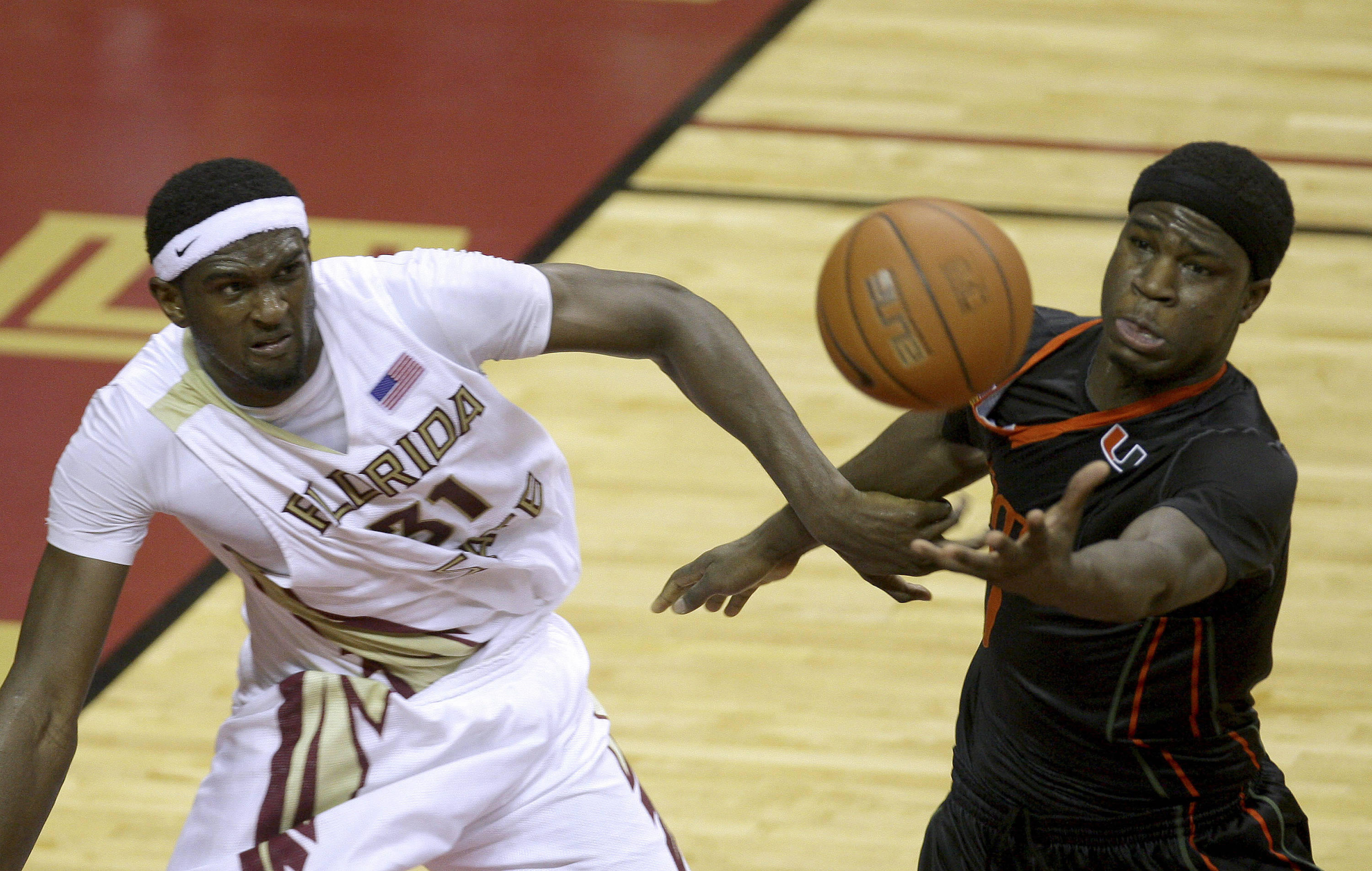 Miami's Adrian Thomas, right, pulls down a second-half rebound against Florida State's Chris Singleton during an NCAA college basketball game, Saturday, Feb. 6, 2010, in Tallahassee, Fla. Florida State won 71-65. (AP Photo/Phil Coale)