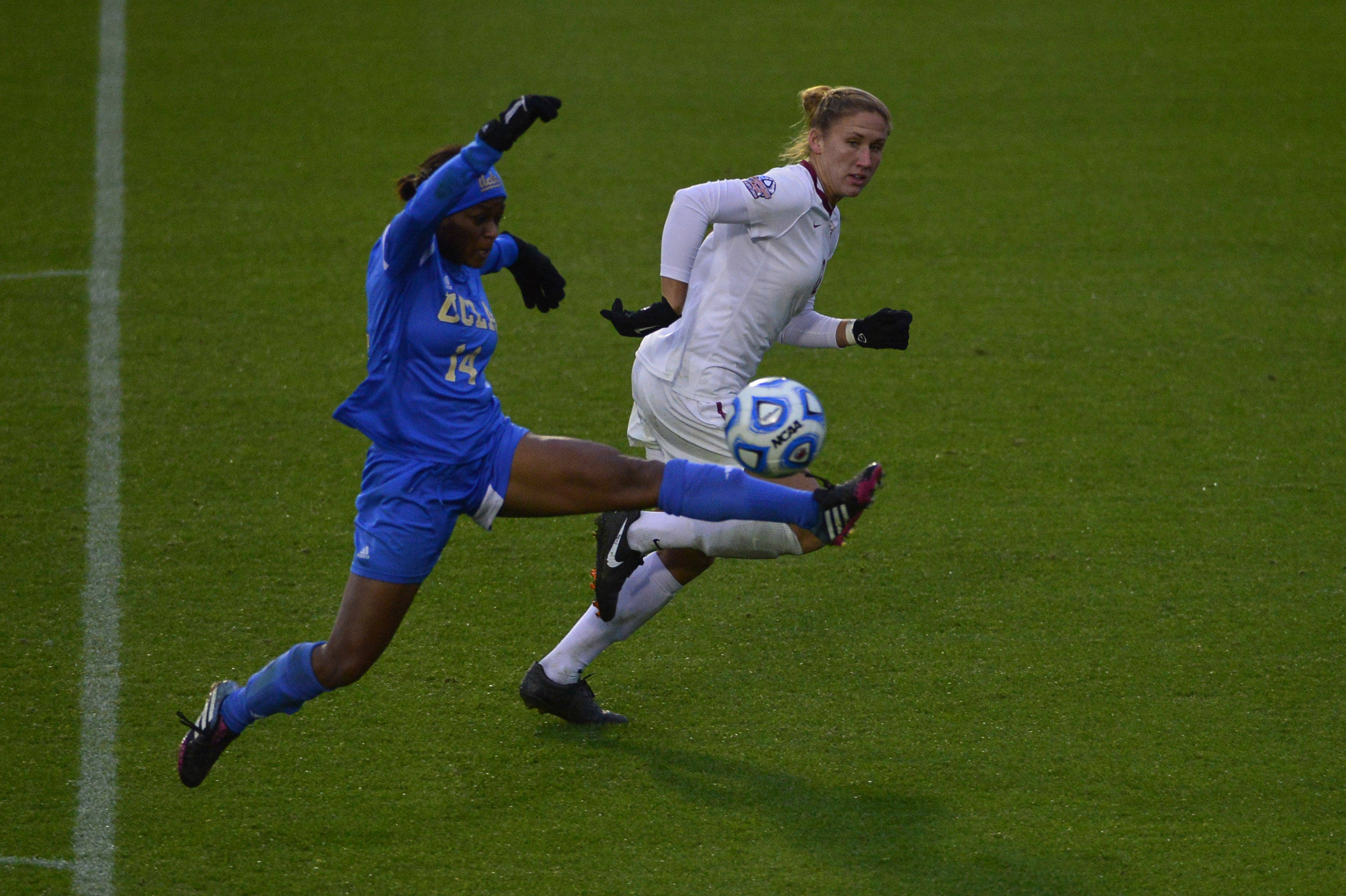 Dec 8, 2013; Cary, NC, USA; UCLA Bruins forward Taylor Smith (14) kicks the ball as Florida State Seminoles defender/midfielder Kristin Grubka (13) defends. The Bruins defeated the Seminoles 1-0 in overtime at WakeMed Soccer Park. Mandatory Credit: Bob Donnan-USA TODAY Sports