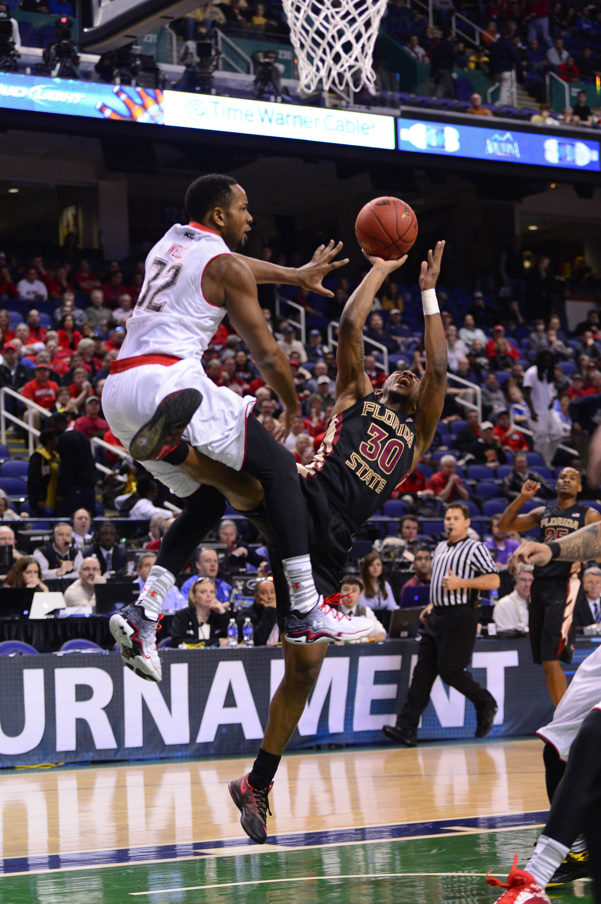 Florida State Seminoles guard Ian Miller (30) shoots as Maryland Terrapins guard/forward Dez Wells (32) defends in the first half in the second round of the ACC college basketball tournament at Greensboro Coliseum. Mandatory Credit: Bob Donnan-USA TODAY Sports