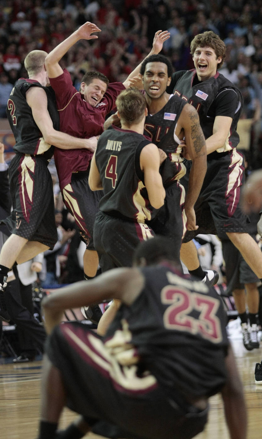 Florida State guard Toney Douglas (23) sits on the court as the rest of his teammates celebrate their 73-70 victory over No. 1 North Carolina in an NCAA college basketball game in the semifinals of the Atlantic Coast Conference men's tournament in Atlanta, Saturday, March 14, 2009. Florida State defeated North Carolina 73-70. (AP Photo/Dave Martin)