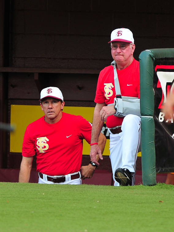 Jamey Shouppe and Mike Martin look over the action from their customary corner spot in the Florida State dugout.