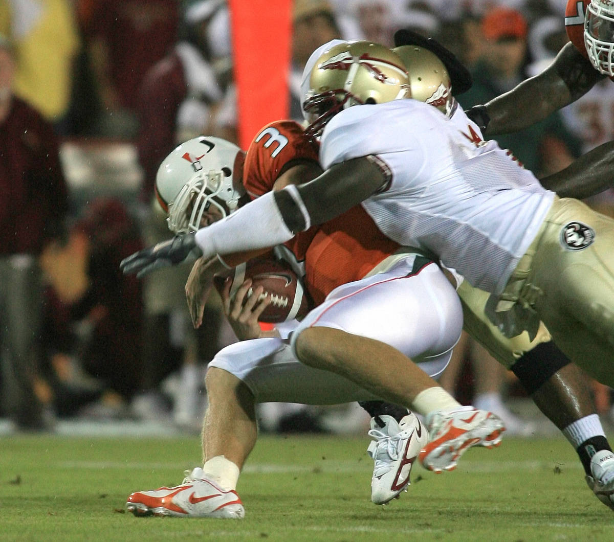Miami quarterback Kyle Wright (3) is sacked by Florida State players Buster Davis, foreground, and Paul Griffin, rear during the first quarter Monday, Sept. 4, 2006 at the Orange Bowl in Miami. (AP Photo/Luis M. Alvarez)