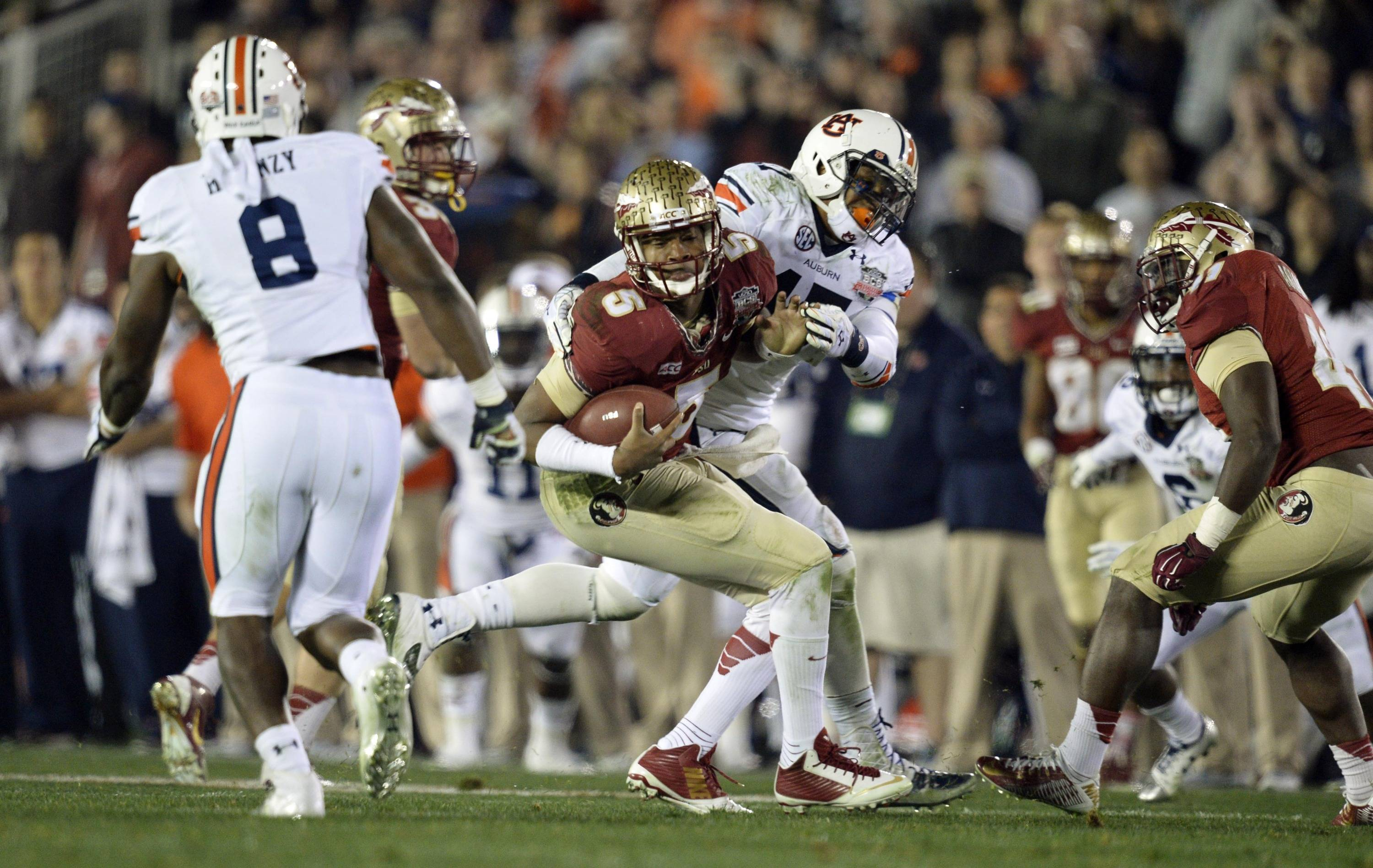 Jan 6, 2014; Pasadena, CA, USA; Florida State Seminoles quarterback Jameis Winston (5) is tackled by Auburn Tigers linebacker Kris Frost (17) during the second half of the 2014 BCS National Championship game at the Rose Bowl.  Mandatory Credit: Robert Hanashiro-USA TODAY Sports