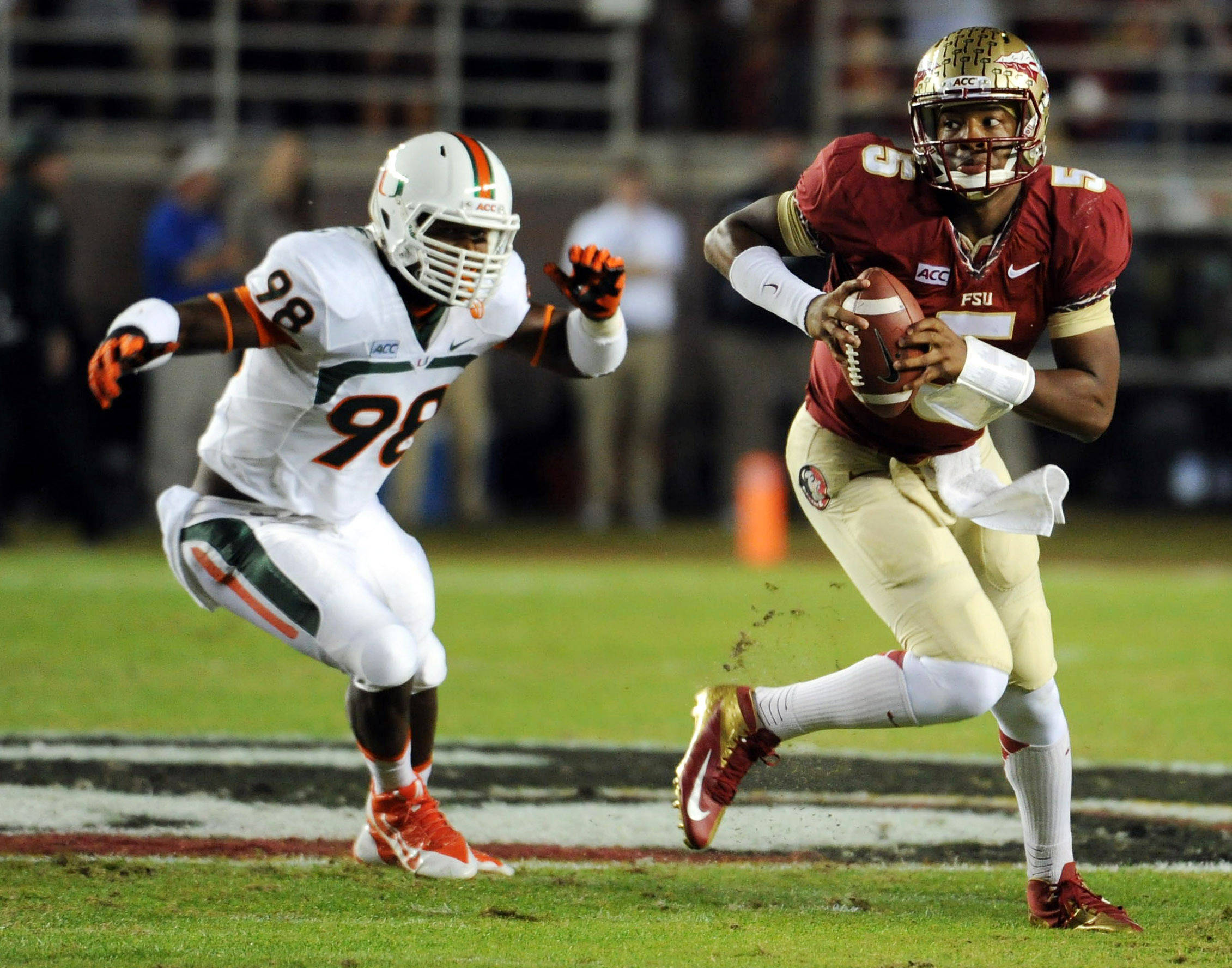 Florida State Seminoles quarterback Jameis Winston (5) runs the ball past Miami Hurricanes defensive end Al-Quadin Muhammad (98) during the game at Doak Campbell Stadium. Mandatory Credit: Melina Vastola-USA TODAY Sports