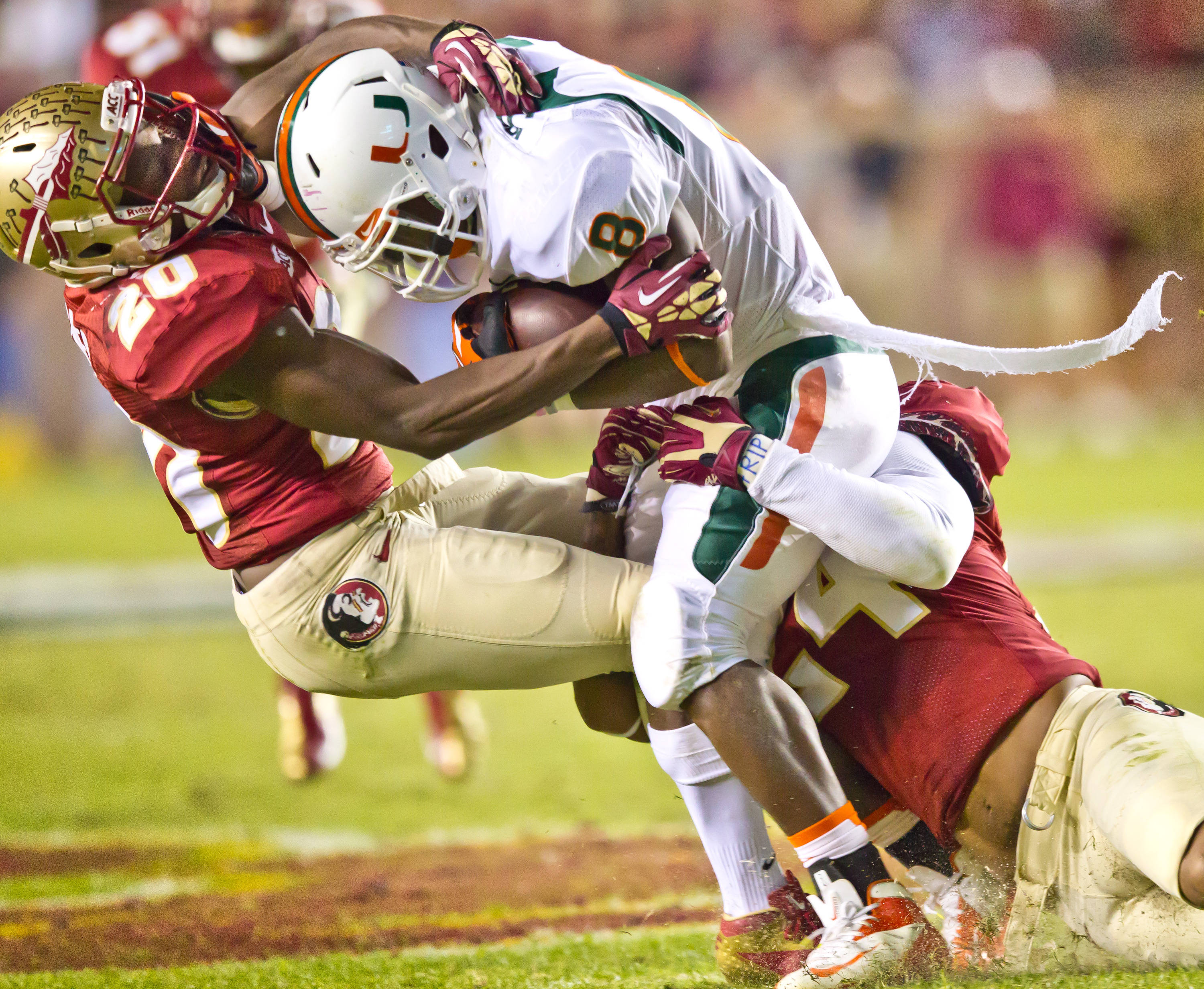 Lamarcus Joyner (20)and Terrance Smith (24) bring down the Canes' Duke Johnson.