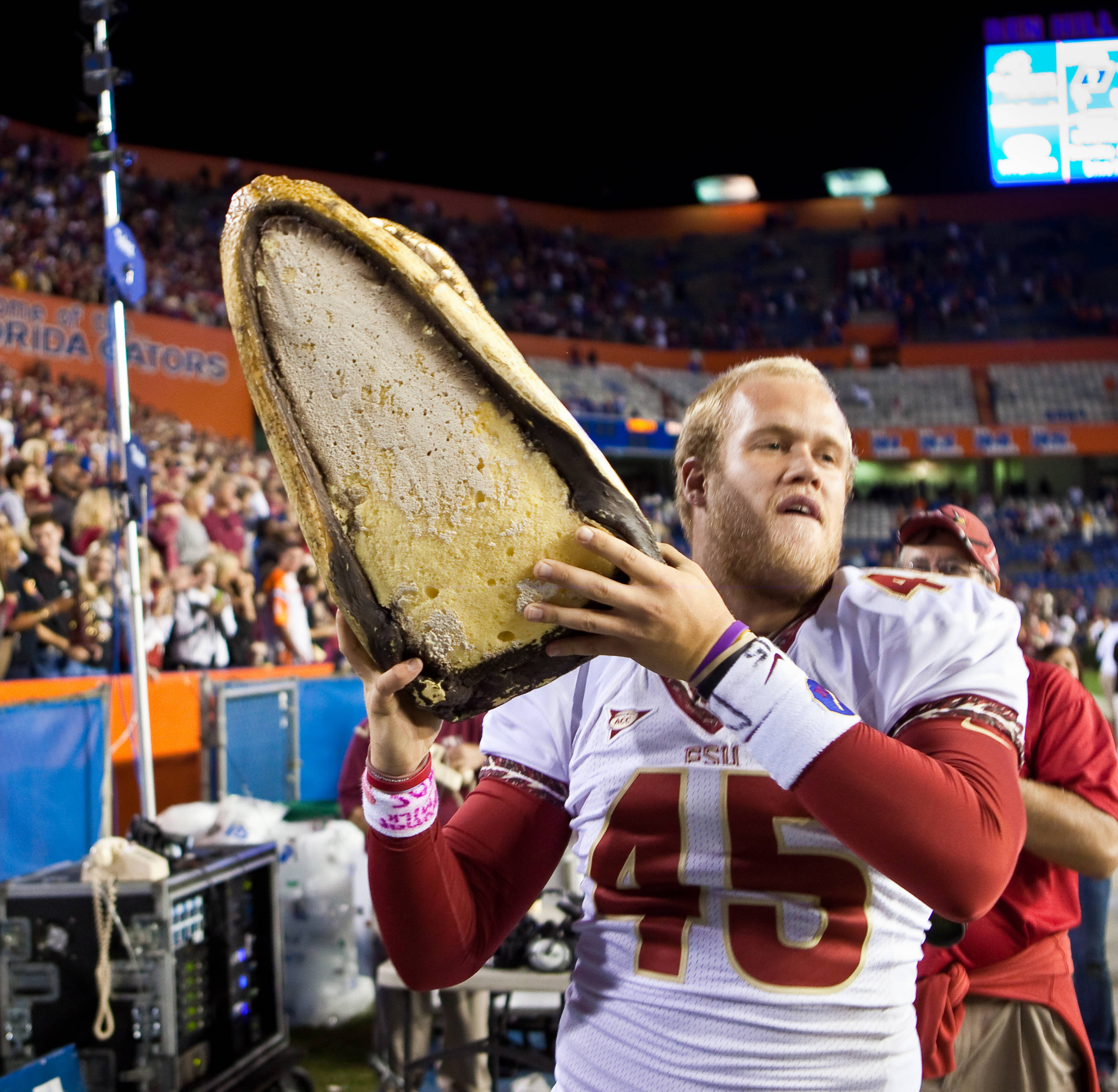 Shawn Powell (45) celebrates by holding the Gator head high