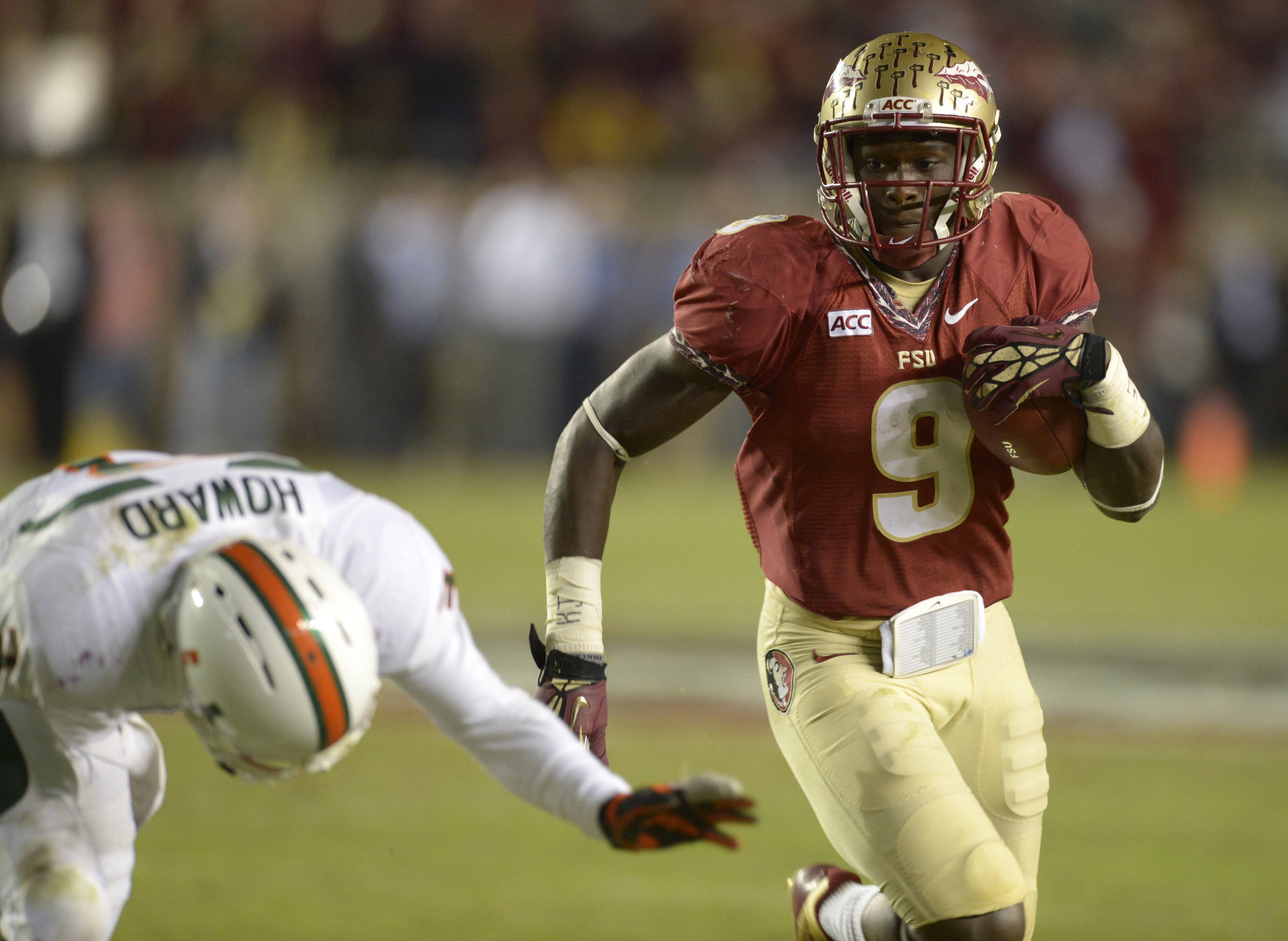 Florida State Seminoles running back Karlos Williams (9) carries past Miami Hurricanes defensive back Tracy Howard (3) during the fourth quarter at Doak Campbell Stadium. The Florida State Seminoles defeated the Miami Hurricanes 41-14. Mandatory Credit: John David Mercer-USA TODAY Sports