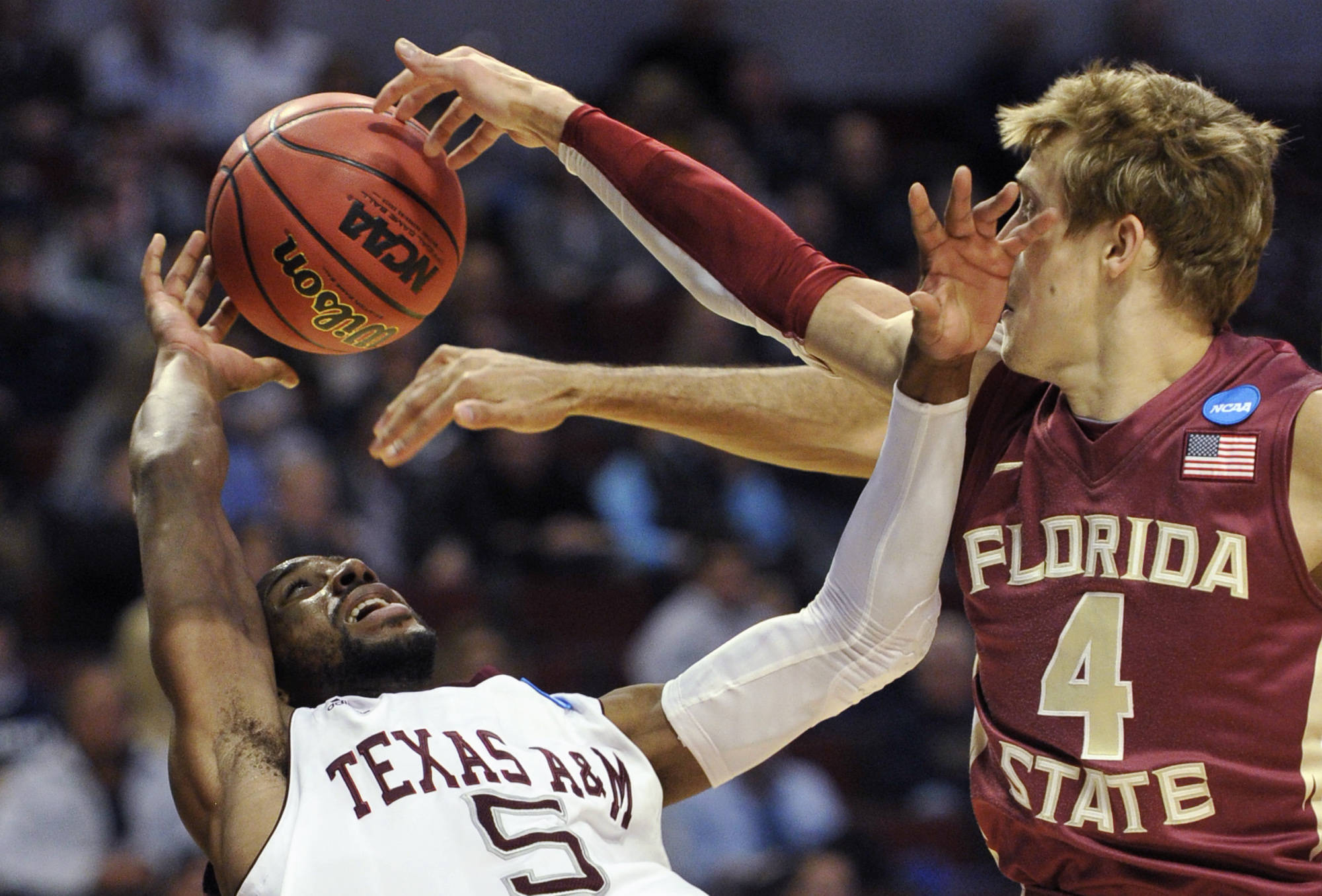 Texas A&M's Dash Harris and Florida State's Deividas Dulkys, of Lithuania, fight for a loose ball in the first half. (AP Photo/Jim Prisching)