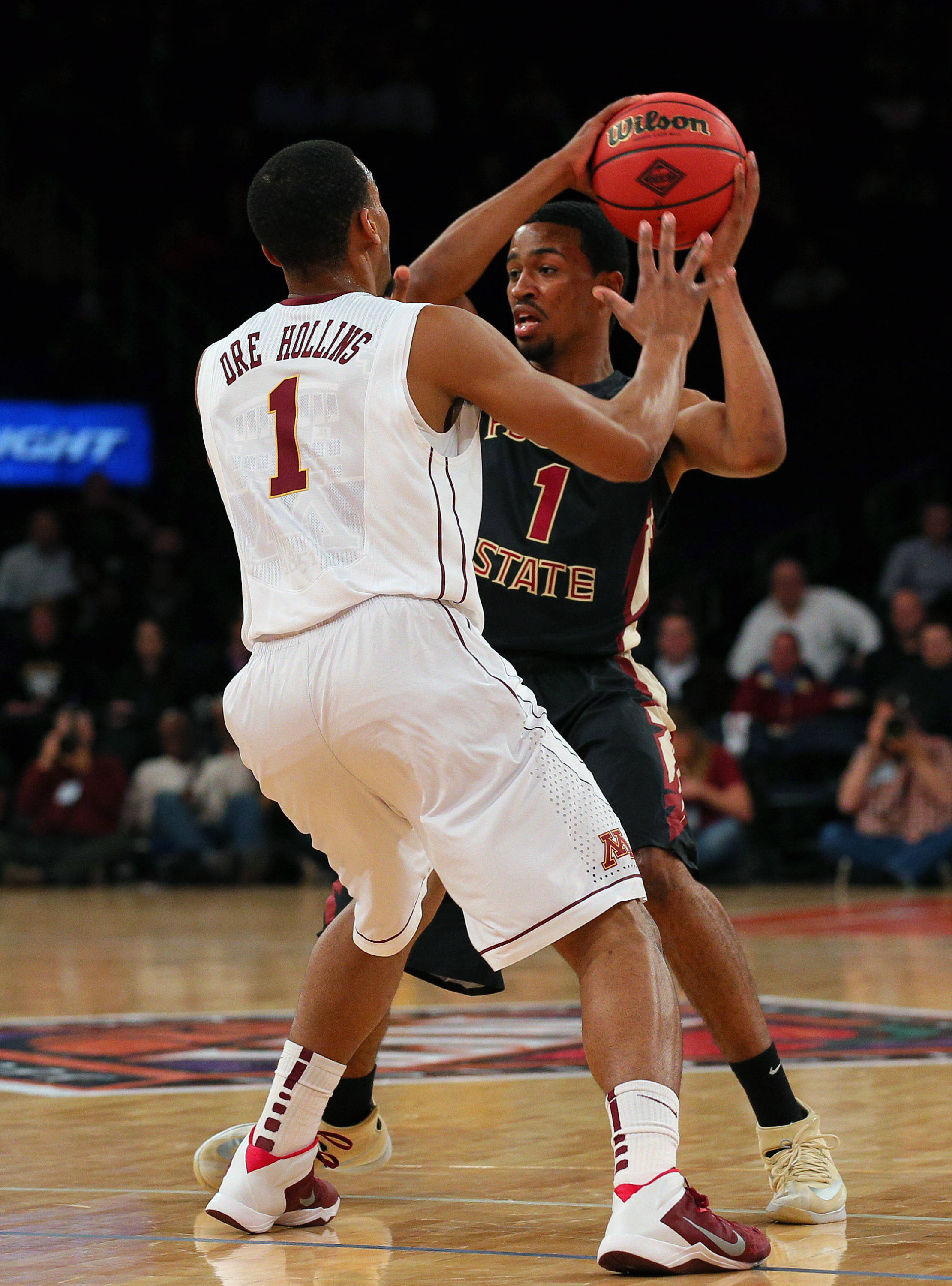 Apr 1, 2014; New York, NY, USA; Florida State Seminoles guard Devon Bookert (1) is defended by Minnesota Golden Gophers guard Andre Hollins (1) during the first half at Madison Square Garden. Mandatory Credit: Adam Hunger-USA TODAY Sports