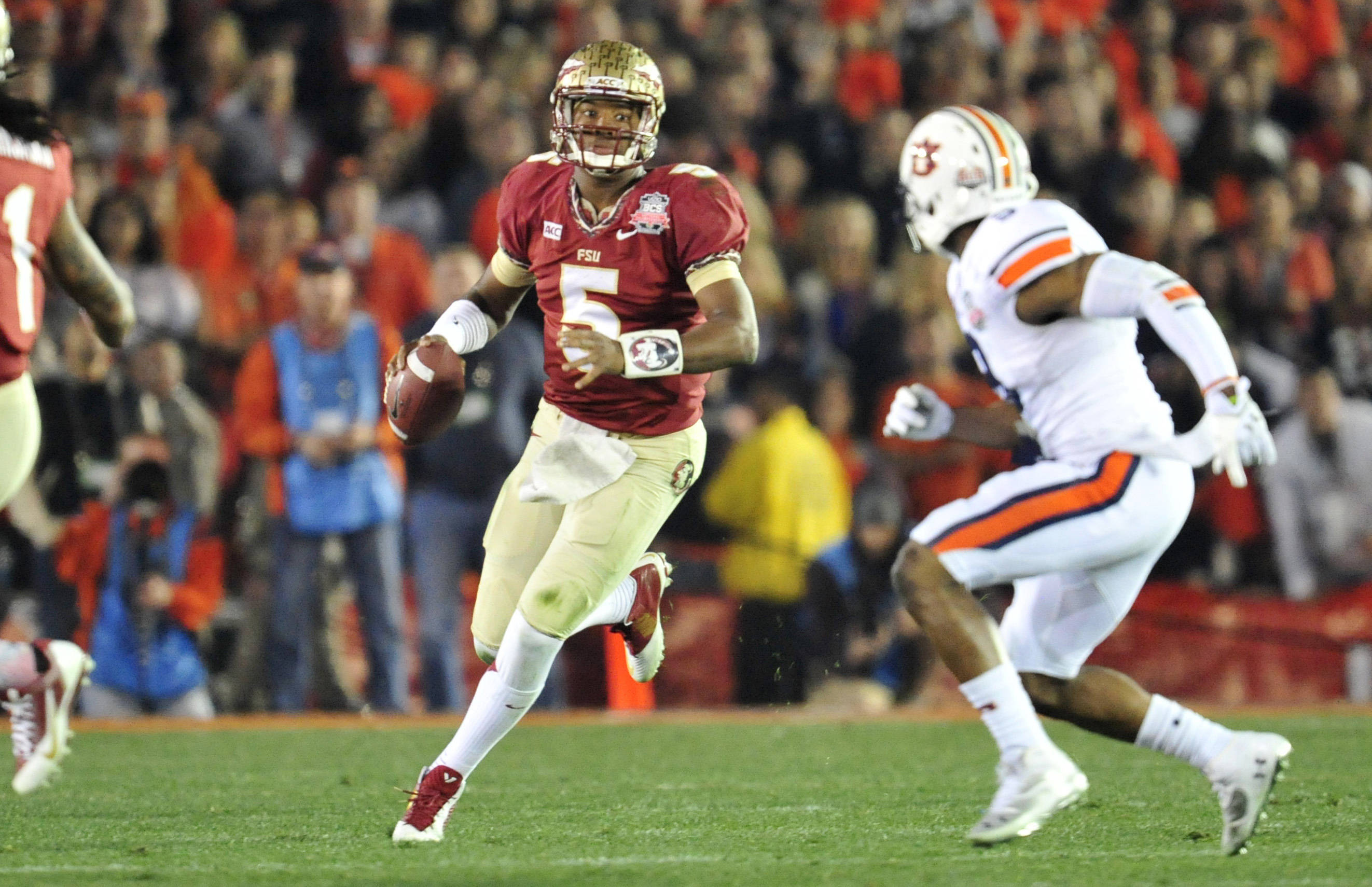 Jan 6, 2014; Pasadena, CA, USA; Florida State Seminoles quarterback Jameis Winston (5) looks to evade Auburn Tigers defense during the second half of the 2014 BCS National Championship game at the Rose Bowl.  Mandatory Credit: Gary A. Vasquez-USA TODAY Sports