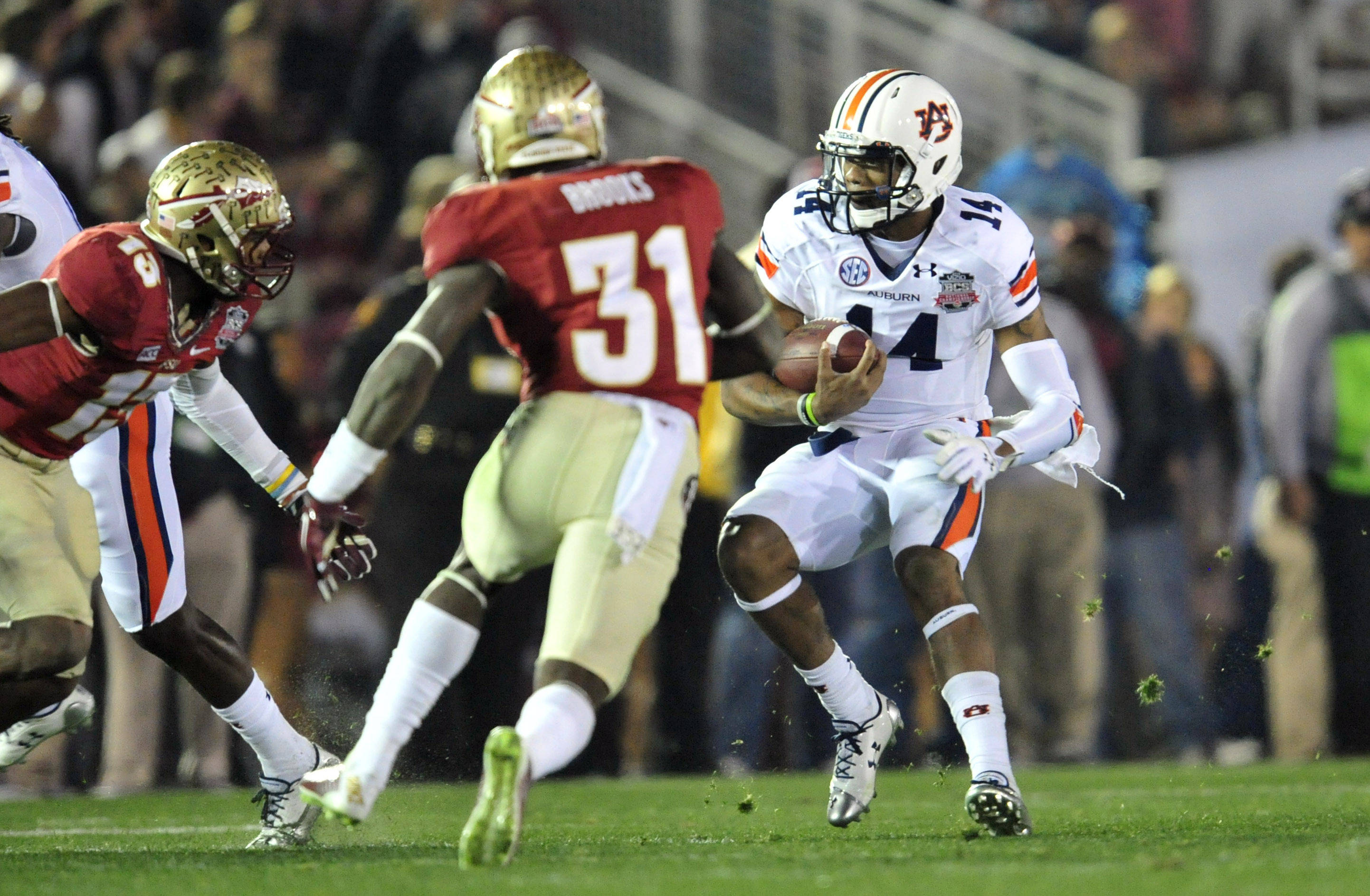 Jan 6, 2014; Pasadena, CA, USA; Auburn Tigers quarterback Nick Marshall (14) tries to evade Florida State Seminoles defense during the first half of the 2014 BCS National Championship game at the Rose Bowl.  Mandatory Credit: Gary A. Vasquez-USA TODAY Sports