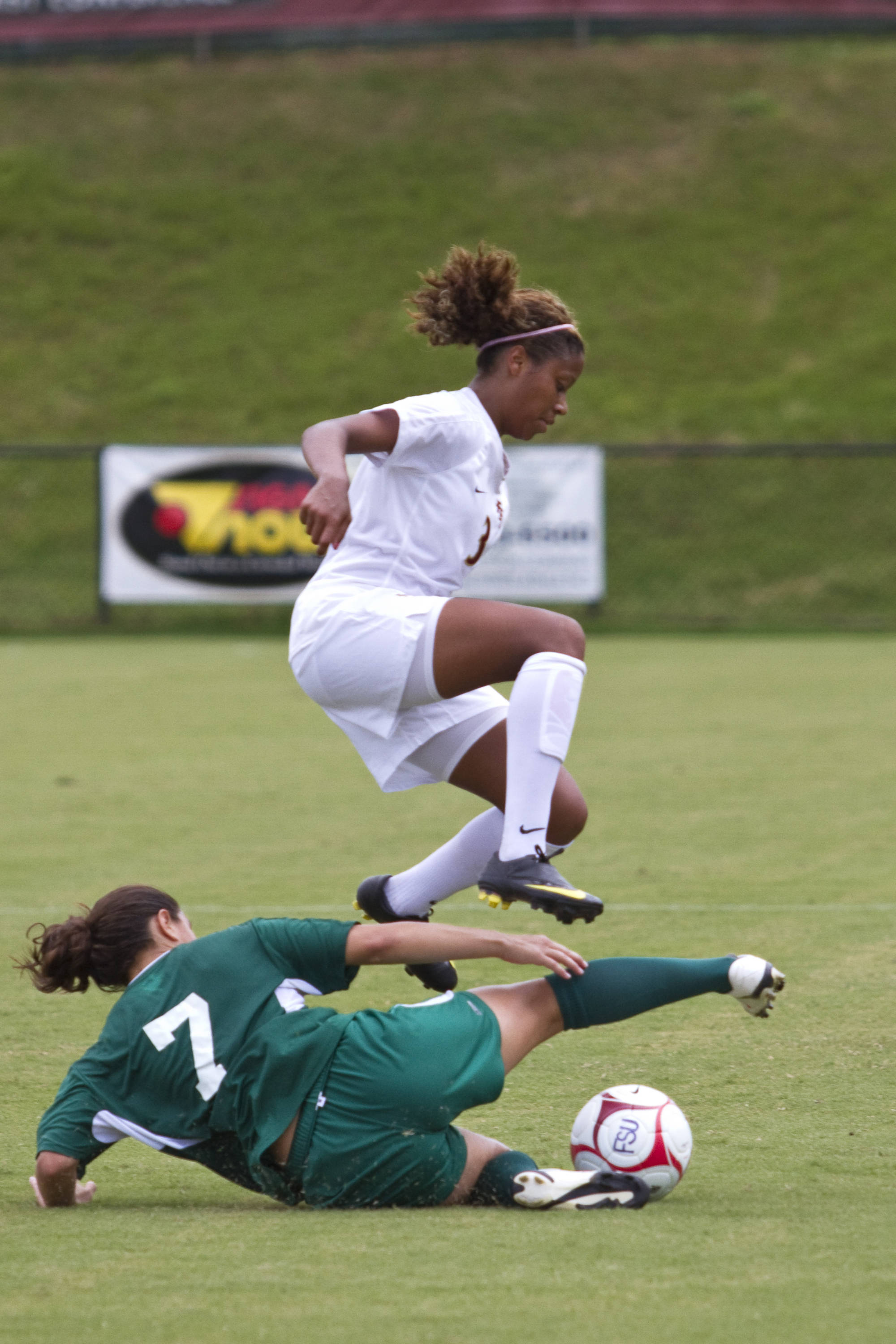 Casey Short (3) jumps as a Stetson player slide tackles her.