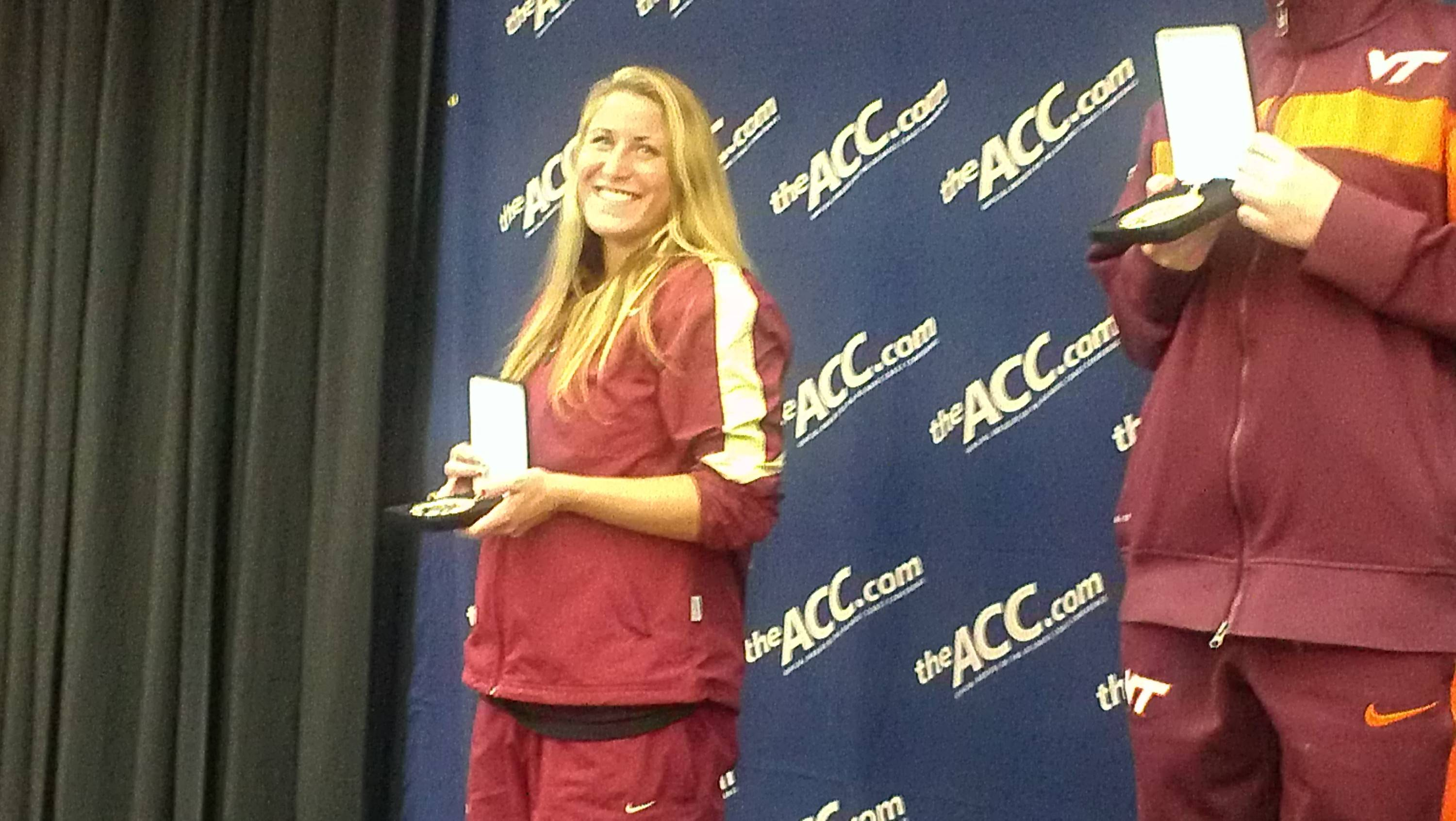 Junior Ariel Rittenhouse shows off her smile as she is awarded the silver medal on the women's one-meter springboard.