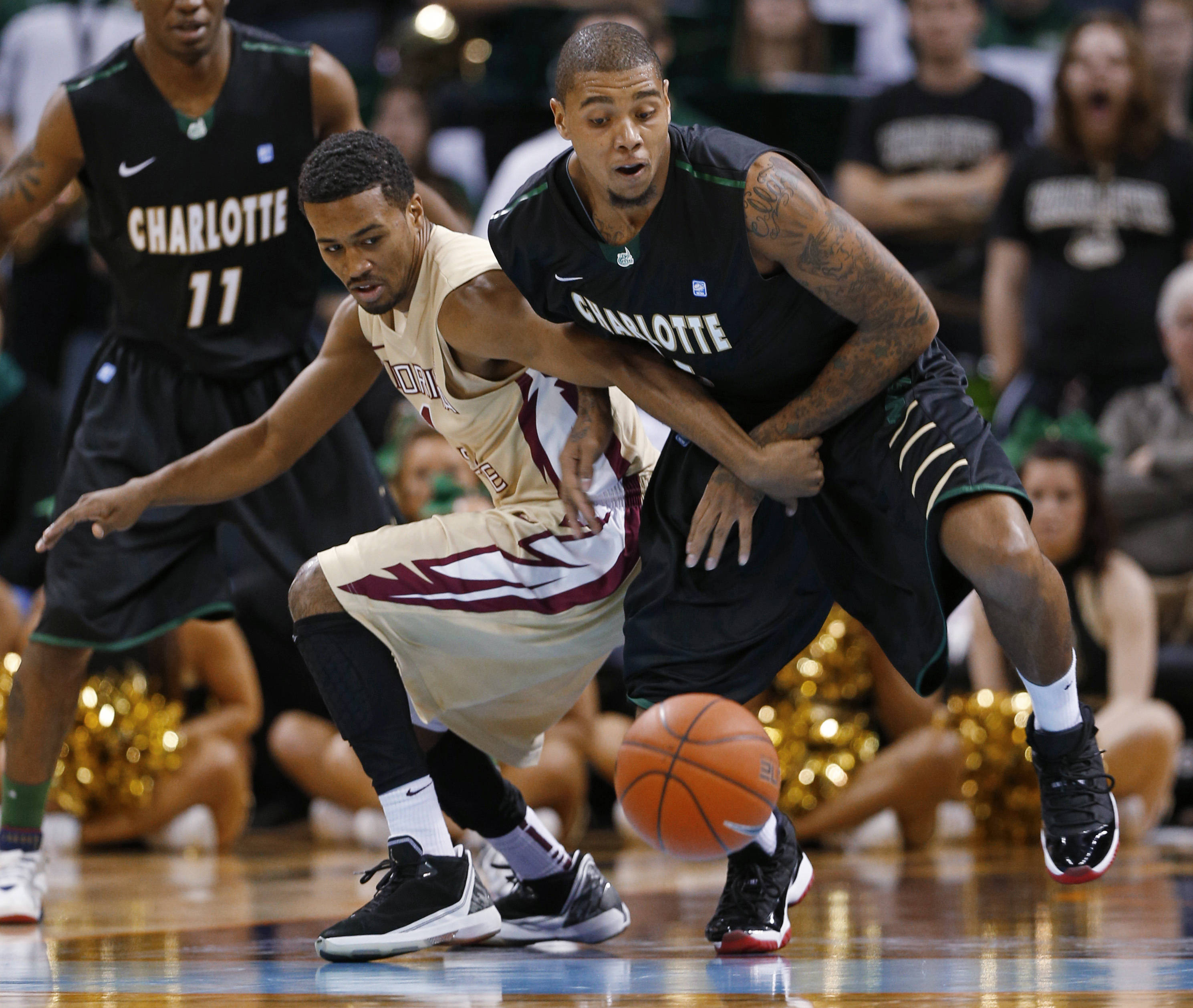 Charlotte's Chris Braswell, right, and Florida State's Devon Bookert, left, chase a loose ball during the second half. (AP Photo/Chuck Burton)